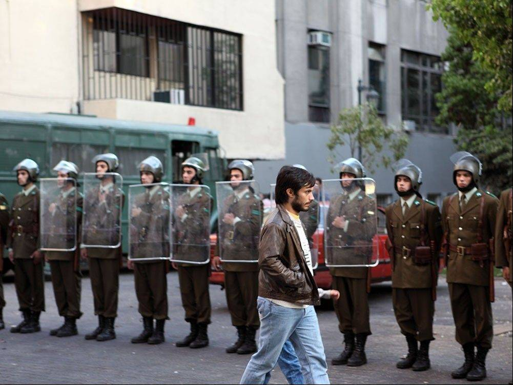 A Chilean public relations expert (Gael Garcia Bernal) passes by troops supporting military dictator Augusto Pinochet in the political drama