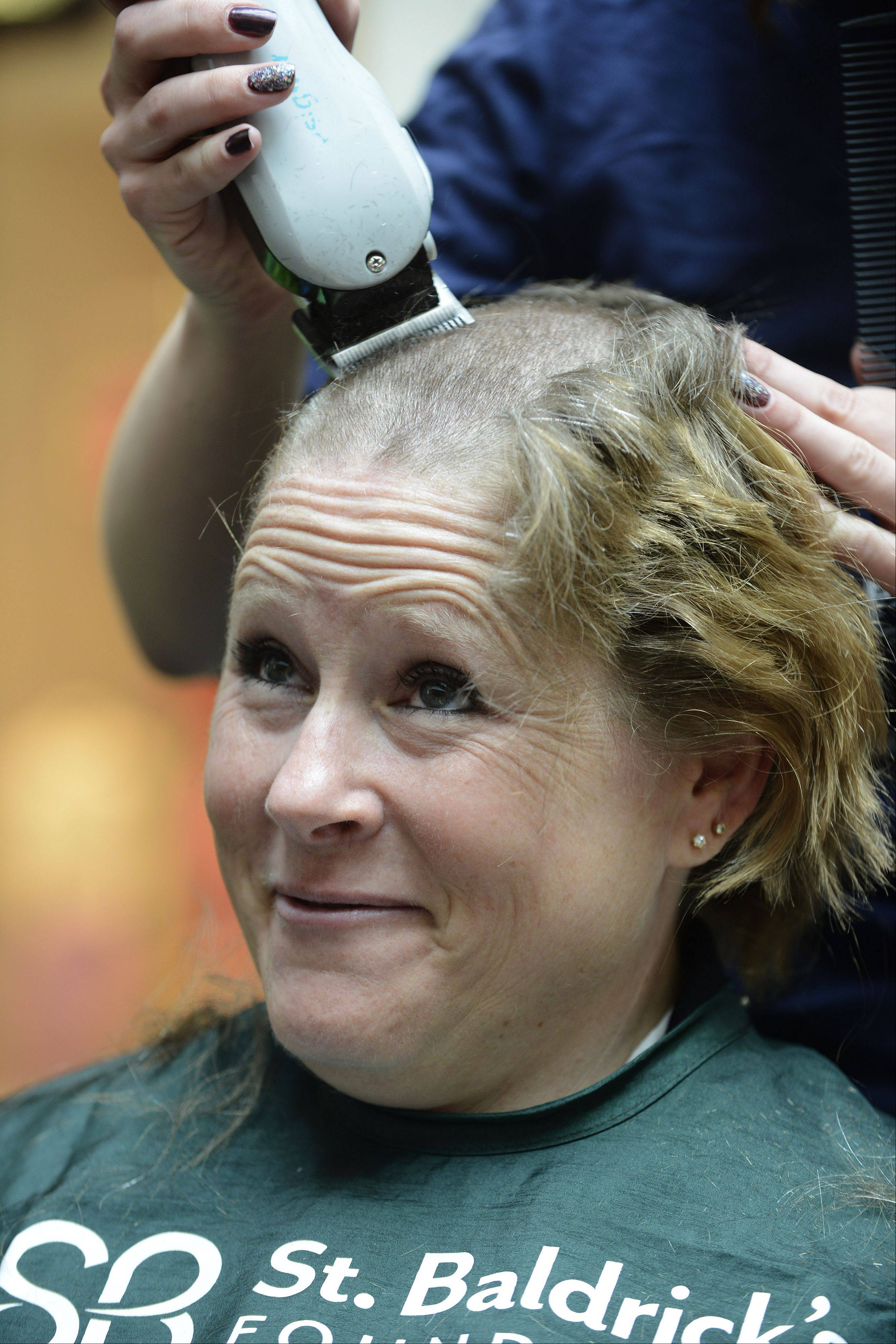 Vernon Hills Police Officer Sharon Joseph has her head shaved during Saturday's St. Baldrick's Foundation fundraiser Westfield Hawthorn Mall in Vernon Hills. Her hair, as well as that of her 9-year old daughter, Kaitlyn, will be donated to Locks of Love.