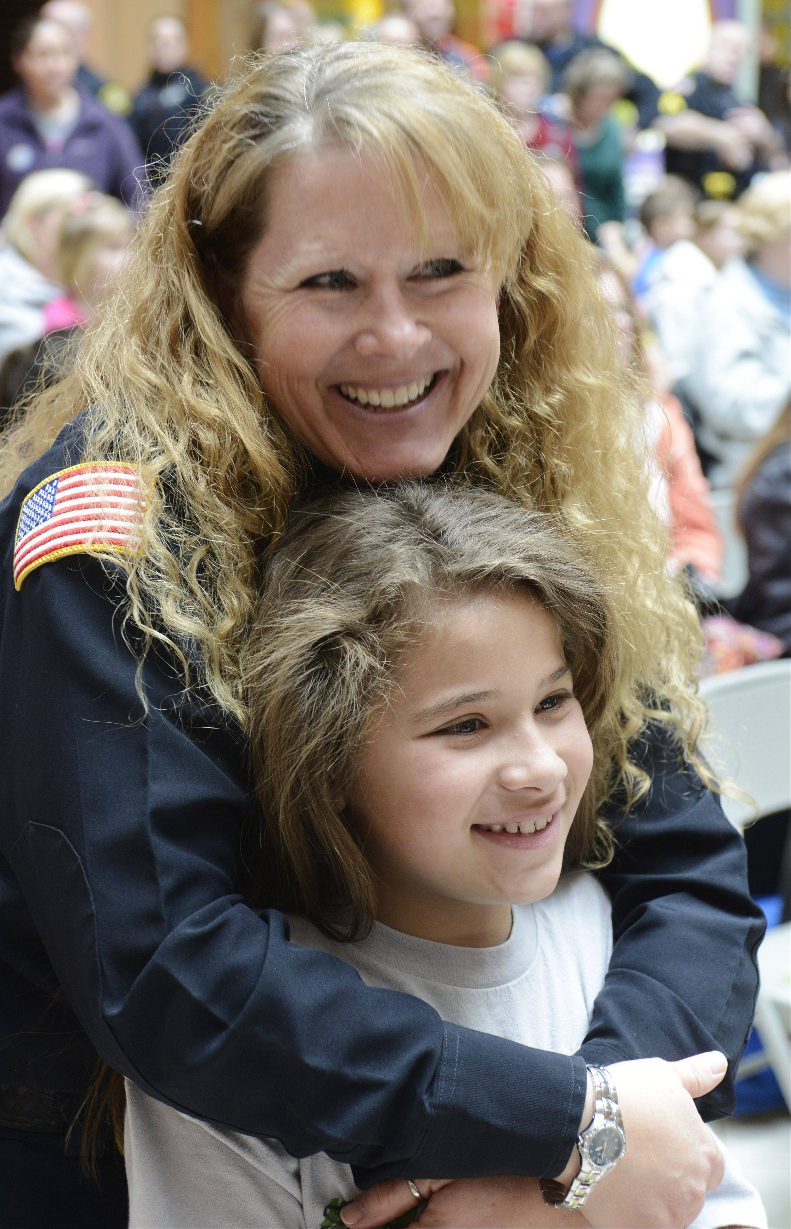 Vernon Hills Police Officer Sharon Joseph and her daughter Kaitlyn, 9, wait for their turns to have their heads shaved during Saturday's St. Baldrick's Foundation festivities at Westfield Hawthorn Mall.