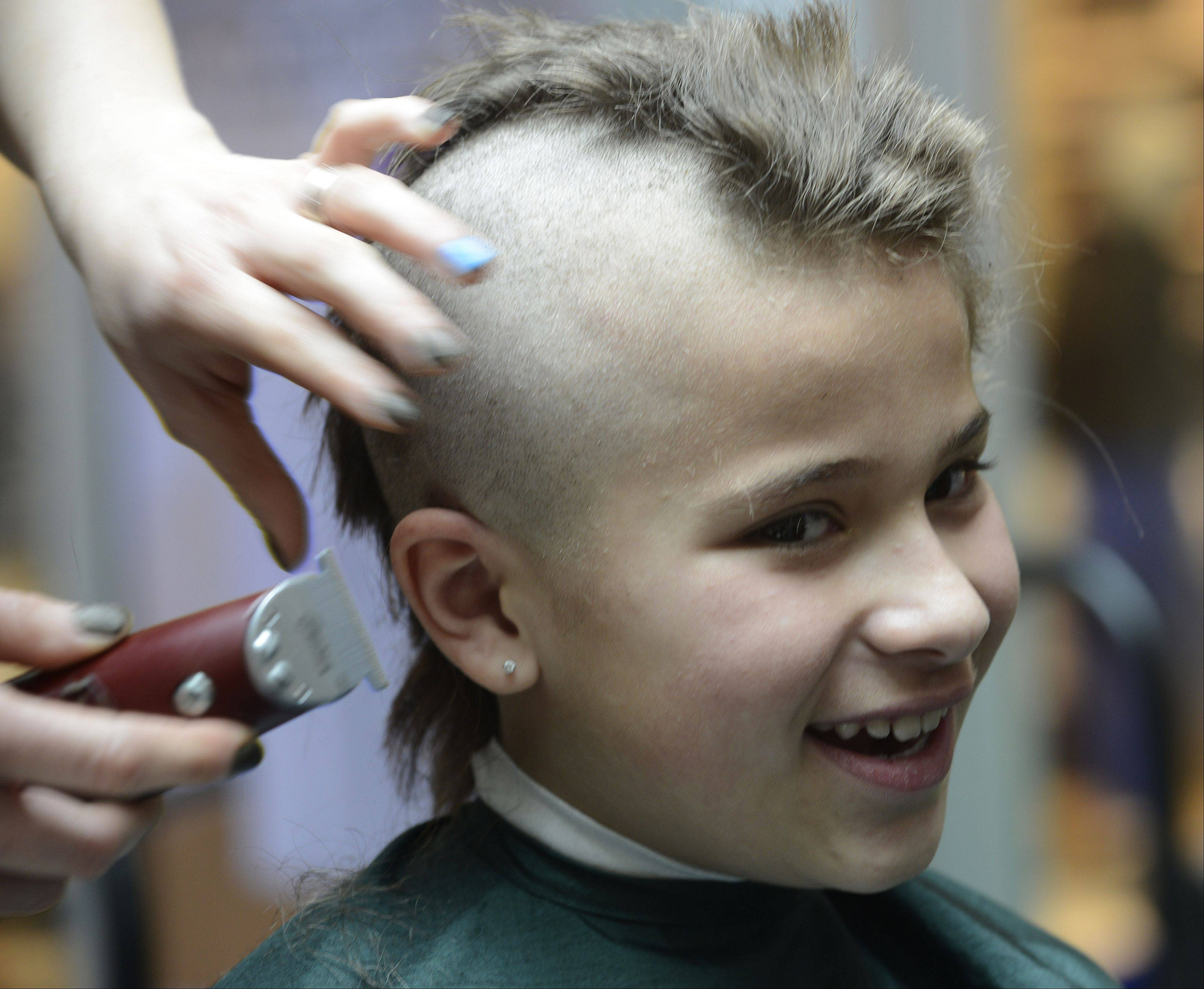 Kaitlyn Joseph, 9, gets her head shaved Saturday at the St. Baldrick's Foundation fundraiser at Westfield Hawthorn Mall in Vernon Hills.