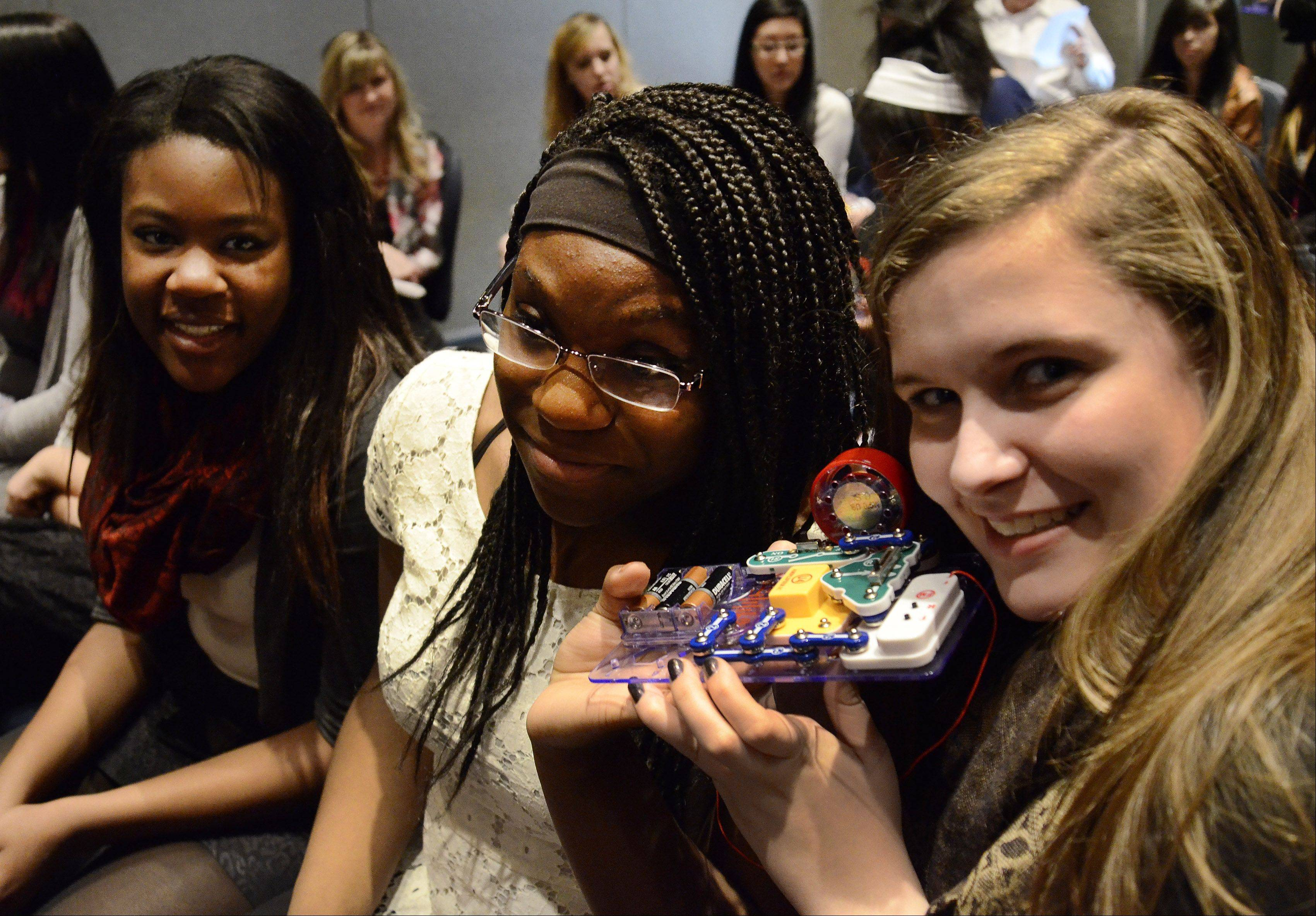 South Elgin High School freshmen from left, Lola Ojomo, Bridgette Williams and Rachel Priore tune in the FM radio they built from a kit Thursday during DeVry University's HerWorld program, educating girls about in-demand STEM (science, technology, engineering, mathematics) careers. The program was at the Stonegate Conference Centre in Hoffman Estates.