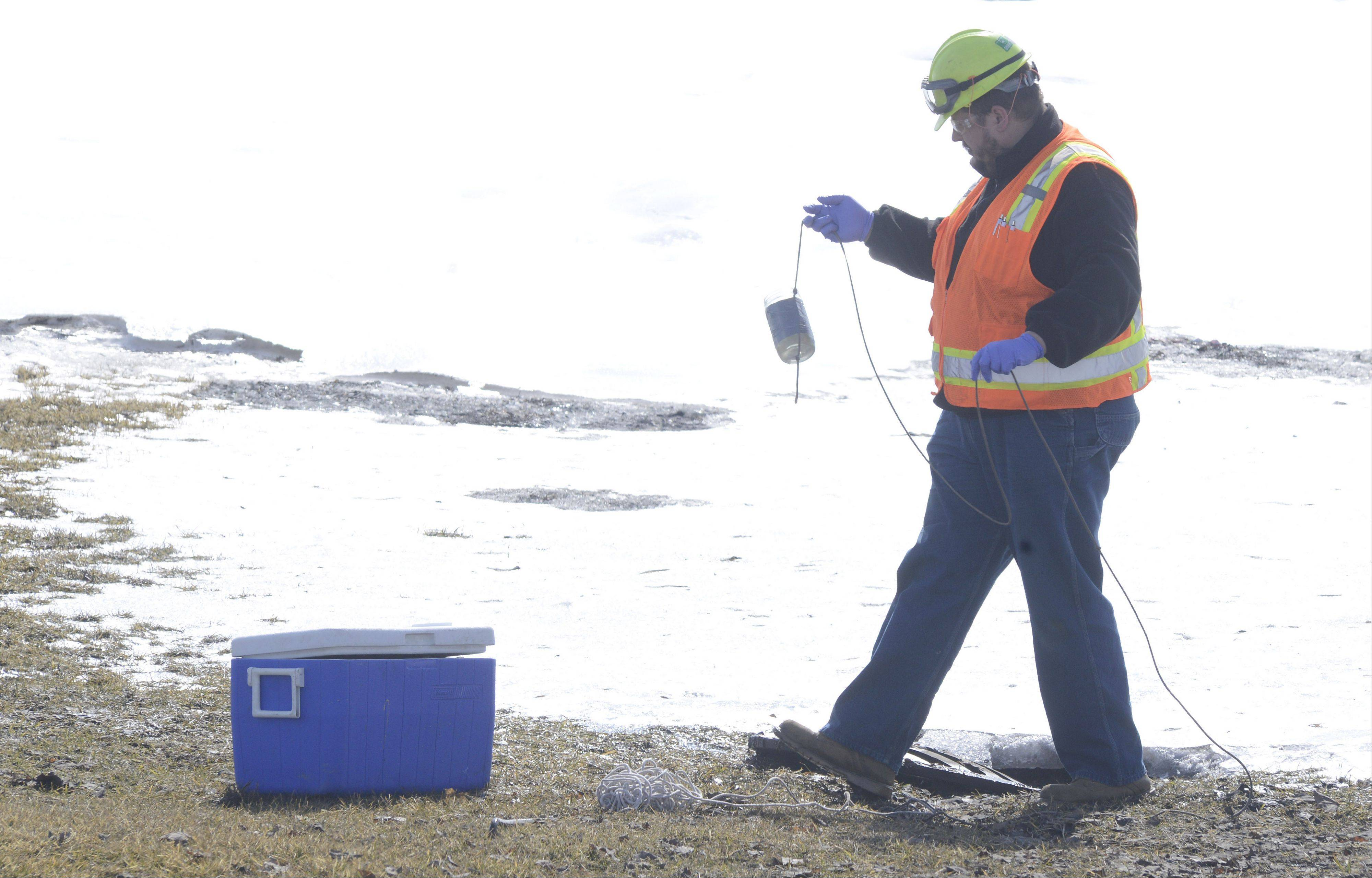 An employee from Environmental Monitoring and Technologies takes water samples from a sewer in a nearby retention pond down the street from Fox Valley Systems Thursday, the day after multiple explosions at the Cary plant.