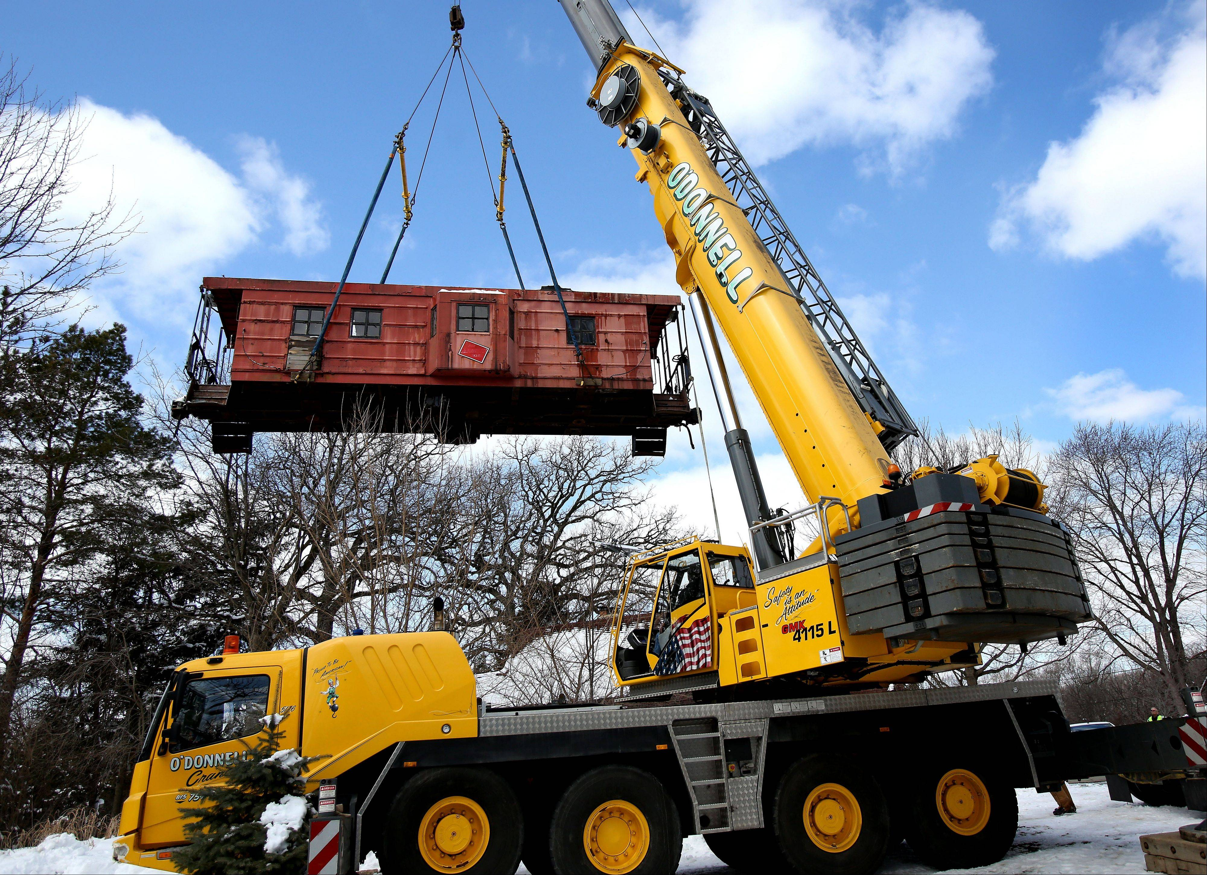 A large crane was needed to lift a caboose onto a flatbed truck Thursday in Itasca. The caboose was moved to its new home at the Itasca Historical Depot Museum.