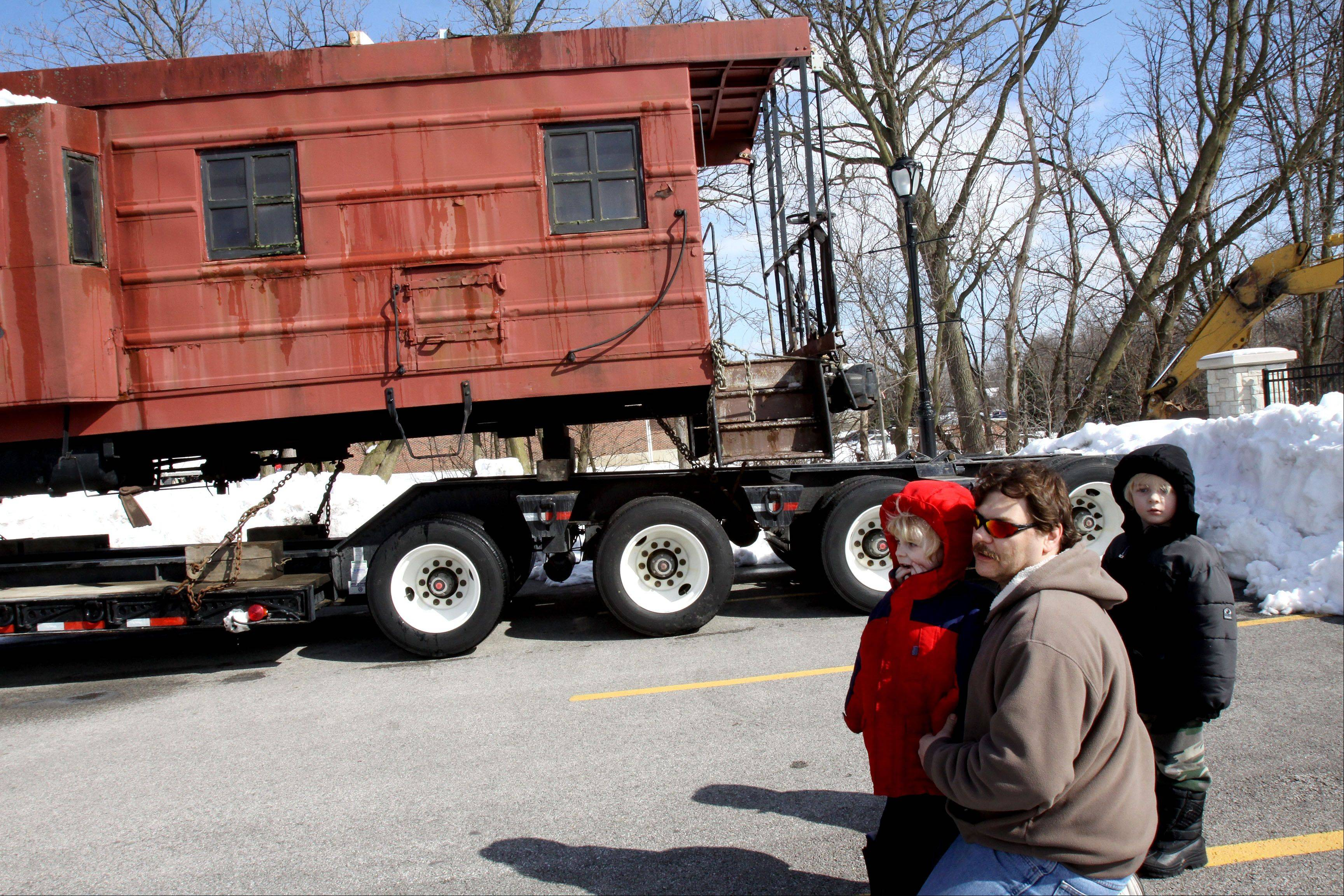 Mike Swintek of Wood Dale brought his twins Michael, left, and Matthew, 4, to see the caboose as it was moved to its new home Thursday at the Itasca Historical Depot Museum.