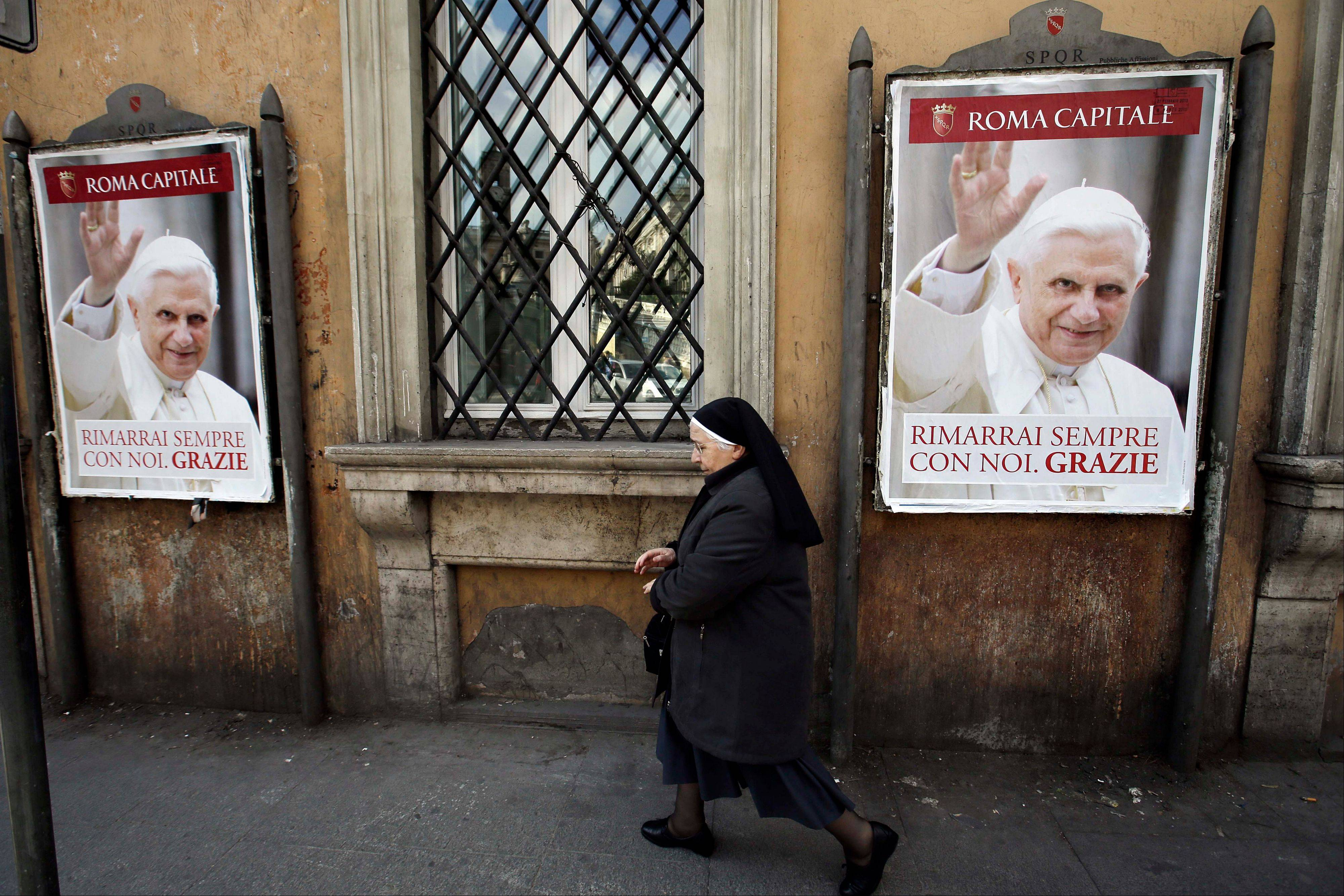 "A nun walks past posters of Pope Benedict XVI reading in Italian, ""You will stay always with us. Thank you"" along a street in Rome."