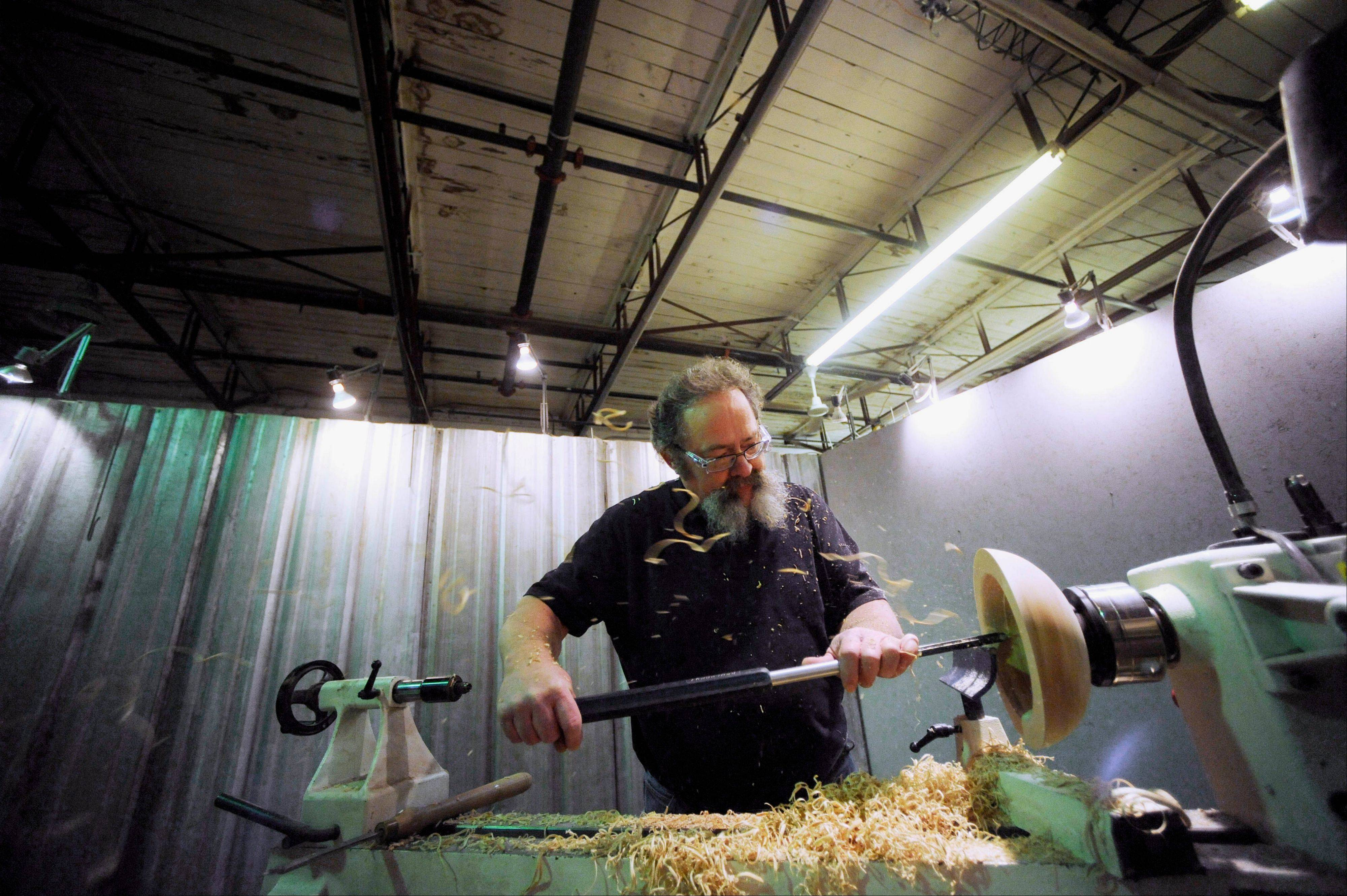 Richard Coers uses a lathe and a chisel to transform a block of wood into a bowl at The Atelier Building in Peoria.