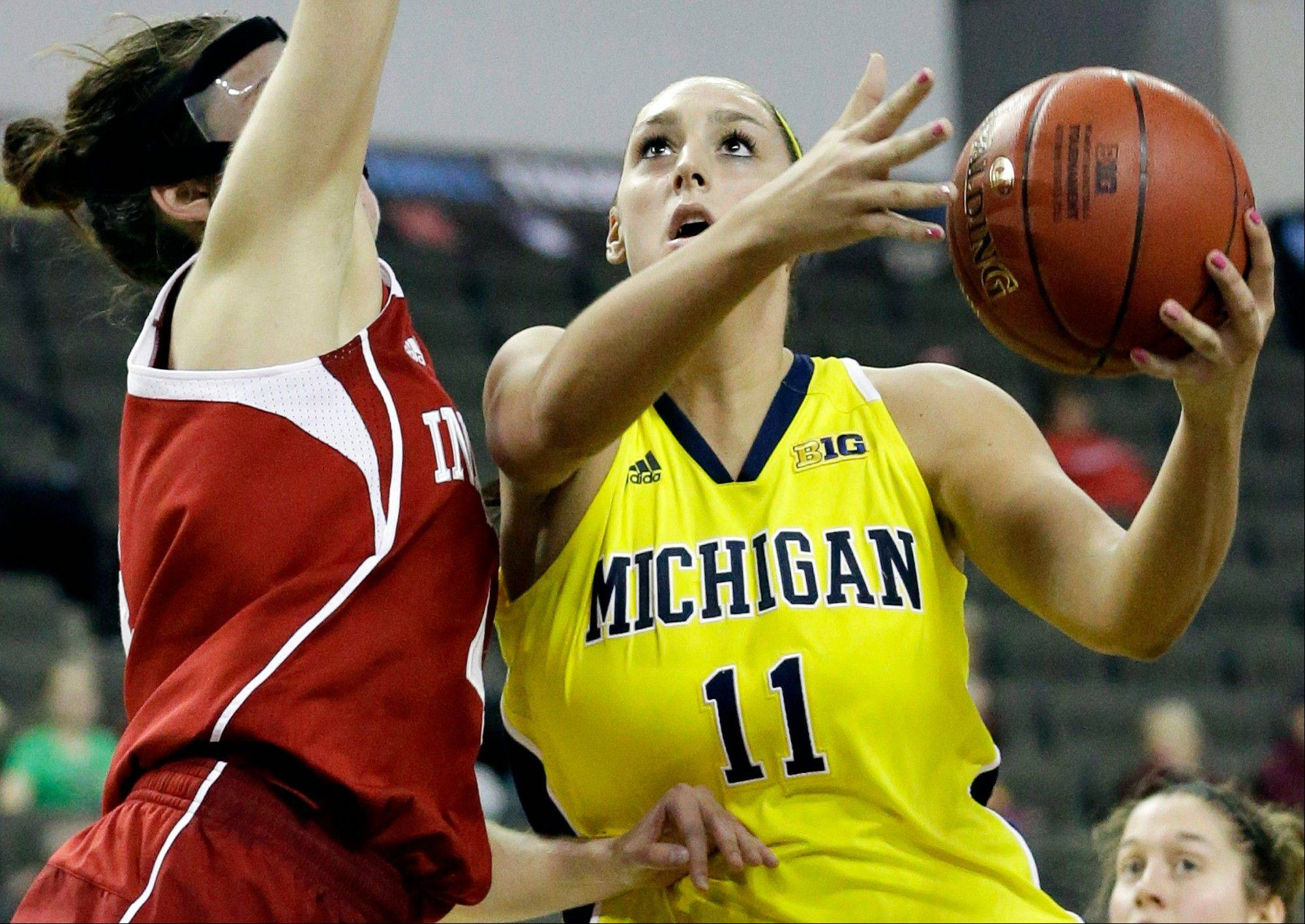 Michigan forward Sam Arnold, right, drives to the basket against Indiana forward Andrea Newbauer during the second half of an NCAA college basketball game in the Big Ten women's tournament in Hoffman Estates Thursday.