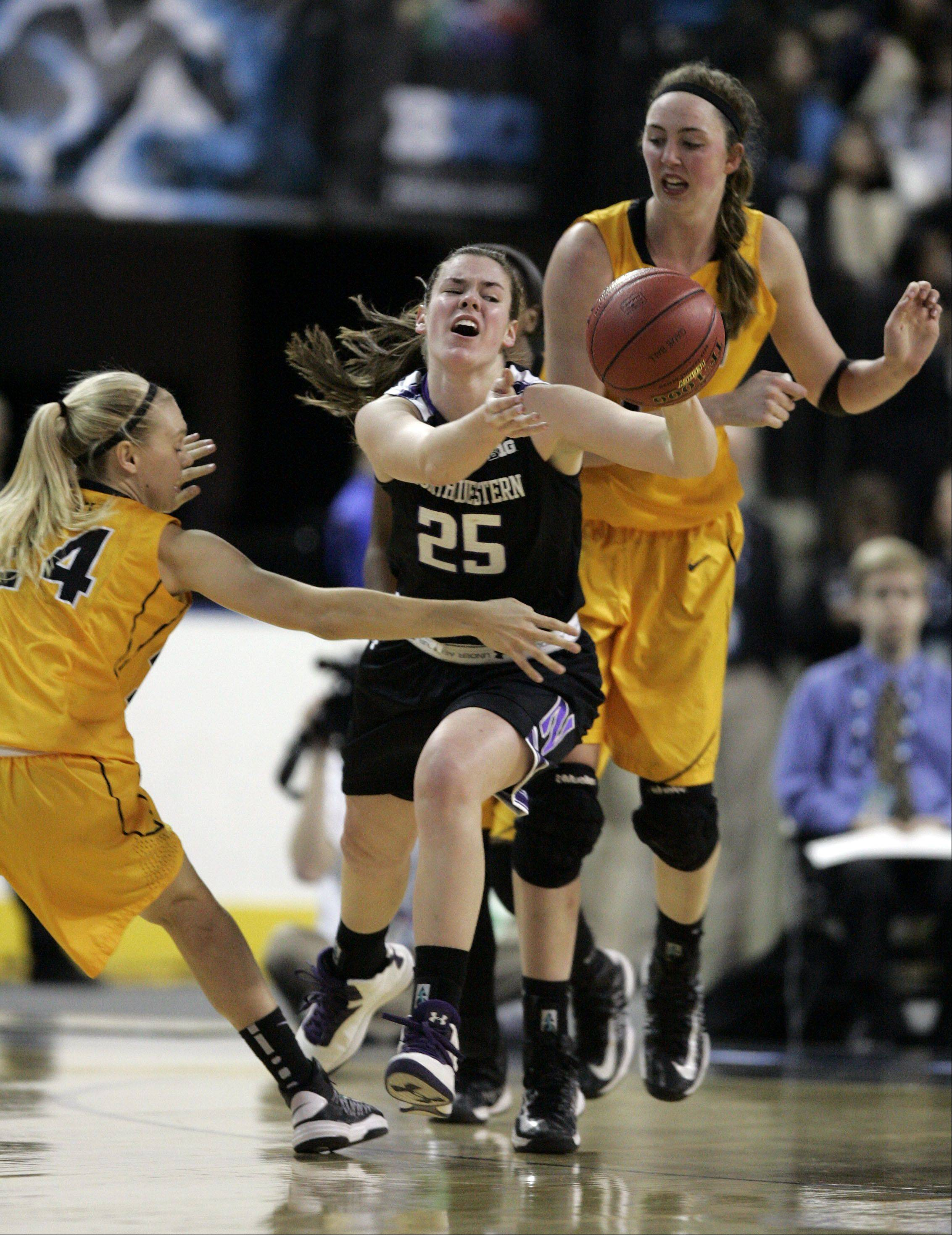 Iowa guard Jaime Printy (24) and center Morgan Johnson (12) pressure Northwestern forward Maggie Lyon during Northwestern's 60-55 loss to the Hawkeyes Thursday at the Big Ten Women's Basketball Tournament at the Sears Centre in Hoffman Estates.