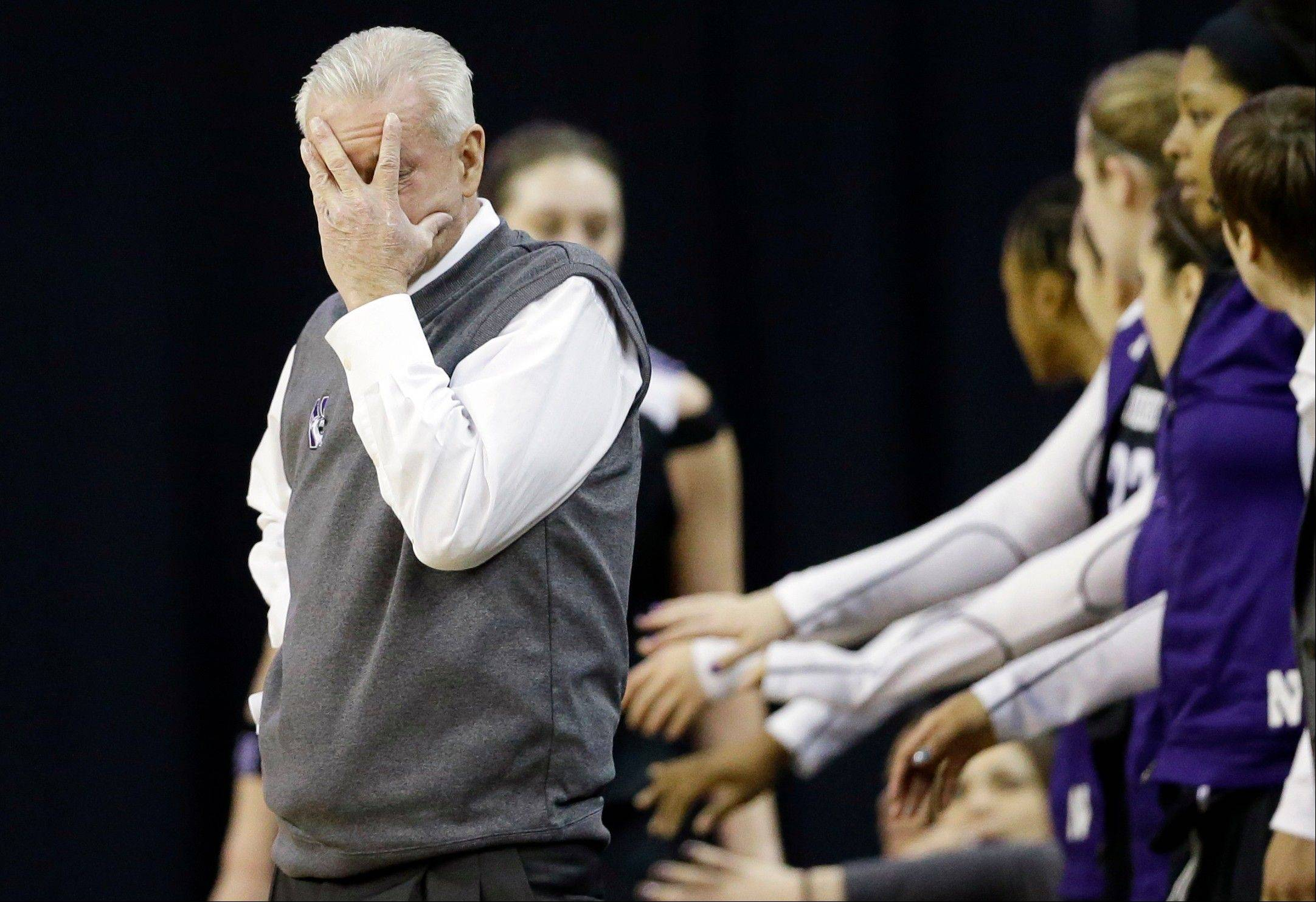 Northwestern head coach Joe McKeown, left, covers his face as reacts Thursday during the first half in the Big Ten Conference tournament against Iowa at the Sears Centre. Iowa won 60-55.