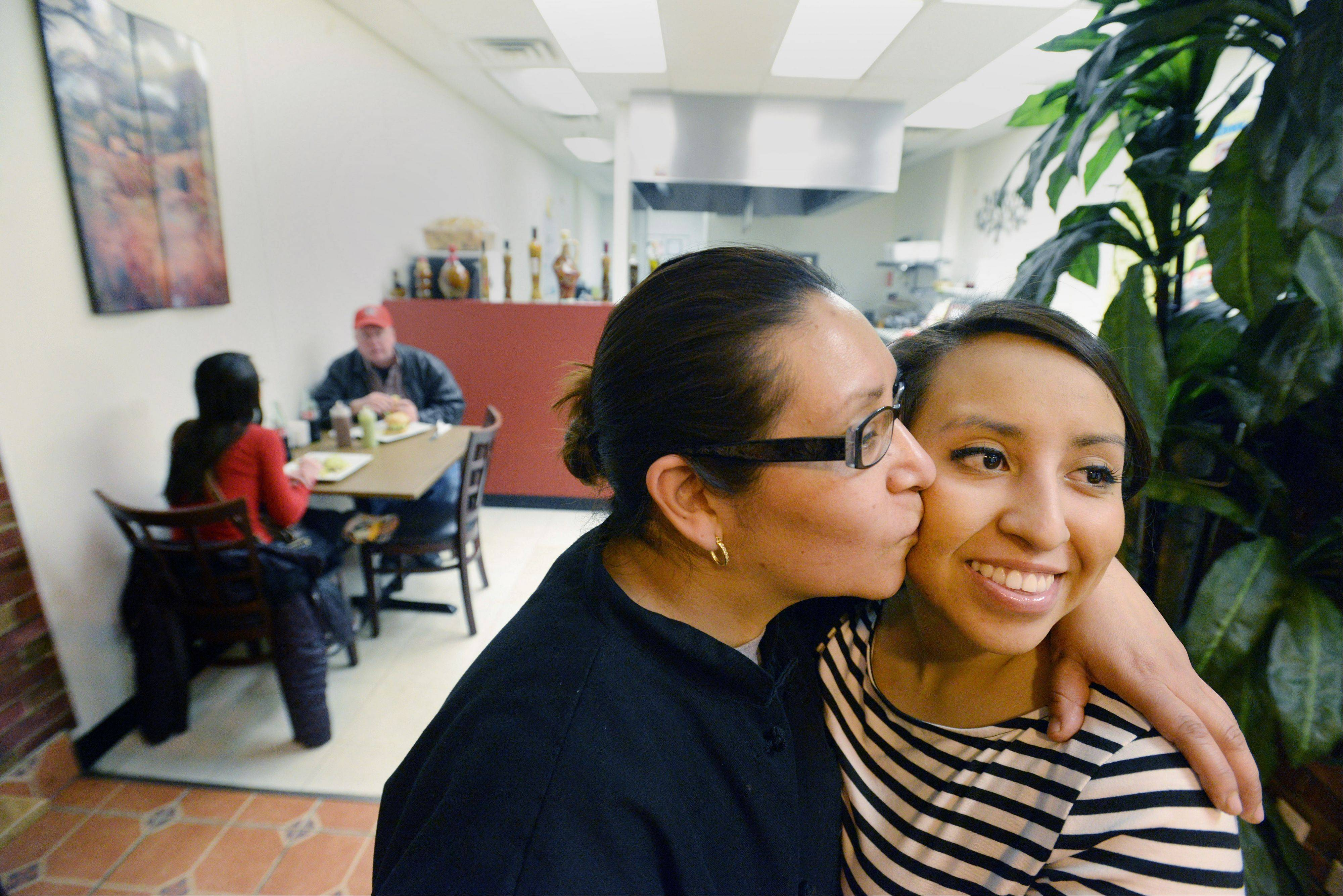 Maribel Molina Cortes hugs and kisses her daughter Mary Ortega during a recent visit. Mary often comes to help her mother run the business. She runs the front so her mother can cook.
