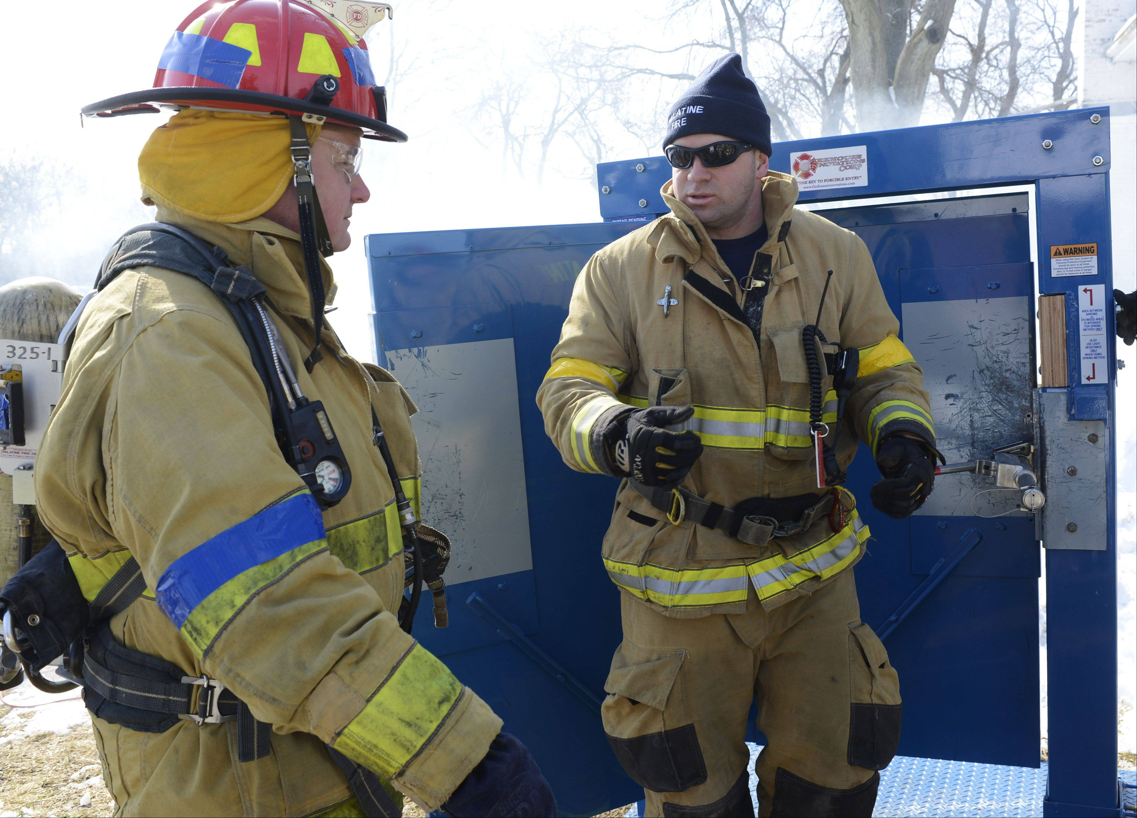 Palatine Village Manager Reid Ottesen, left, learns about forcible entry through a doorway from Palatine firefighter/paramedic Kevin Burris. Several elected and appointed officials participated in the fire training session Friday on the former Camelot property in Palatine.