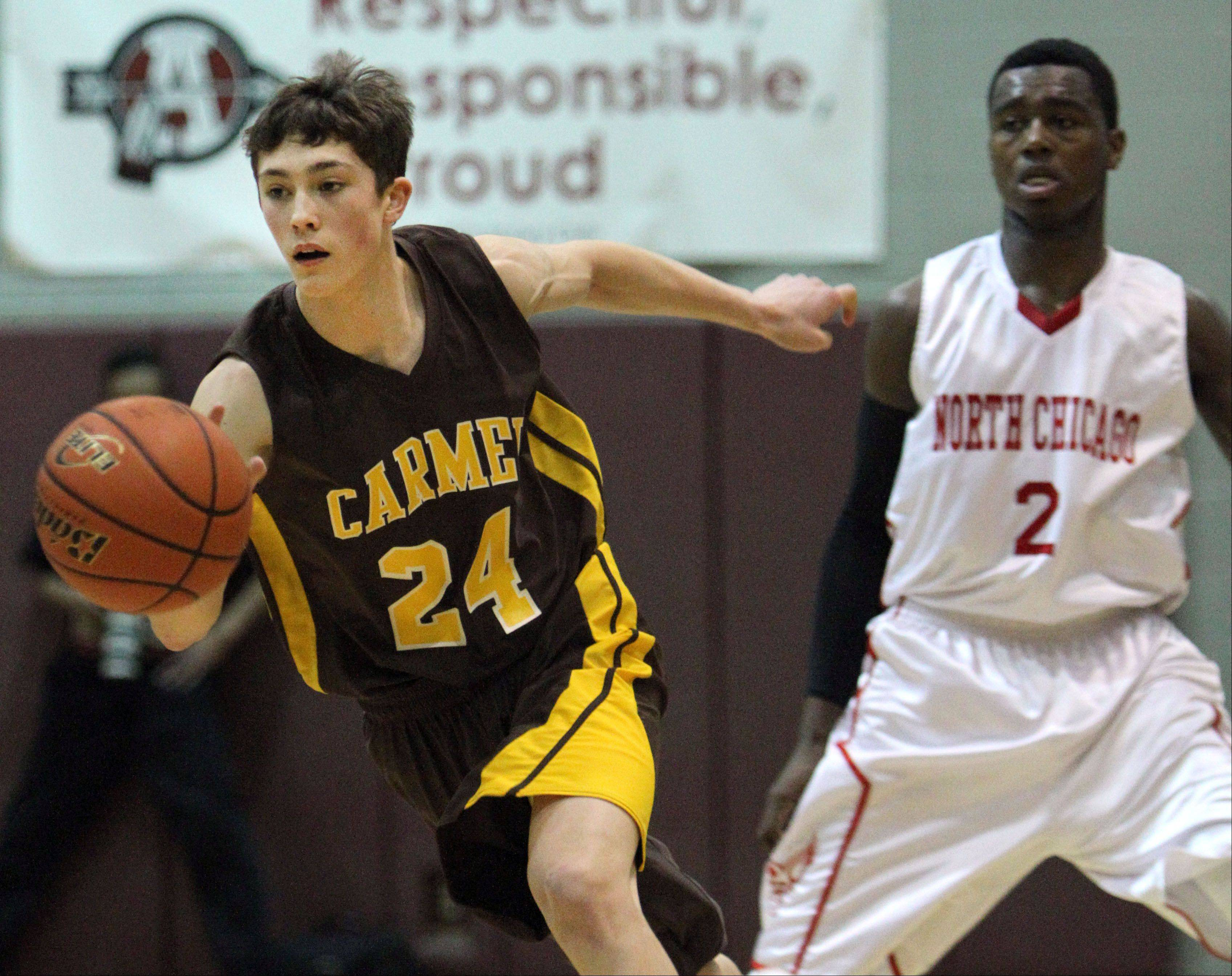 Carmel�s Billy Kirby, left, drives past North Chicago�s JaVairiius Amos-Mays.