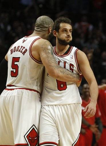Utah Jazz center Al Jefferson (25) dunks over Chicago Bulls center Nazr Mohammed and Joakim Noah (13) as teammate Enes Kanter (0) watches during the first half of an NBA basketball game on Friday, March 8, 2013, in Chicago. (AP Photo/Charles Rex Arbogast)