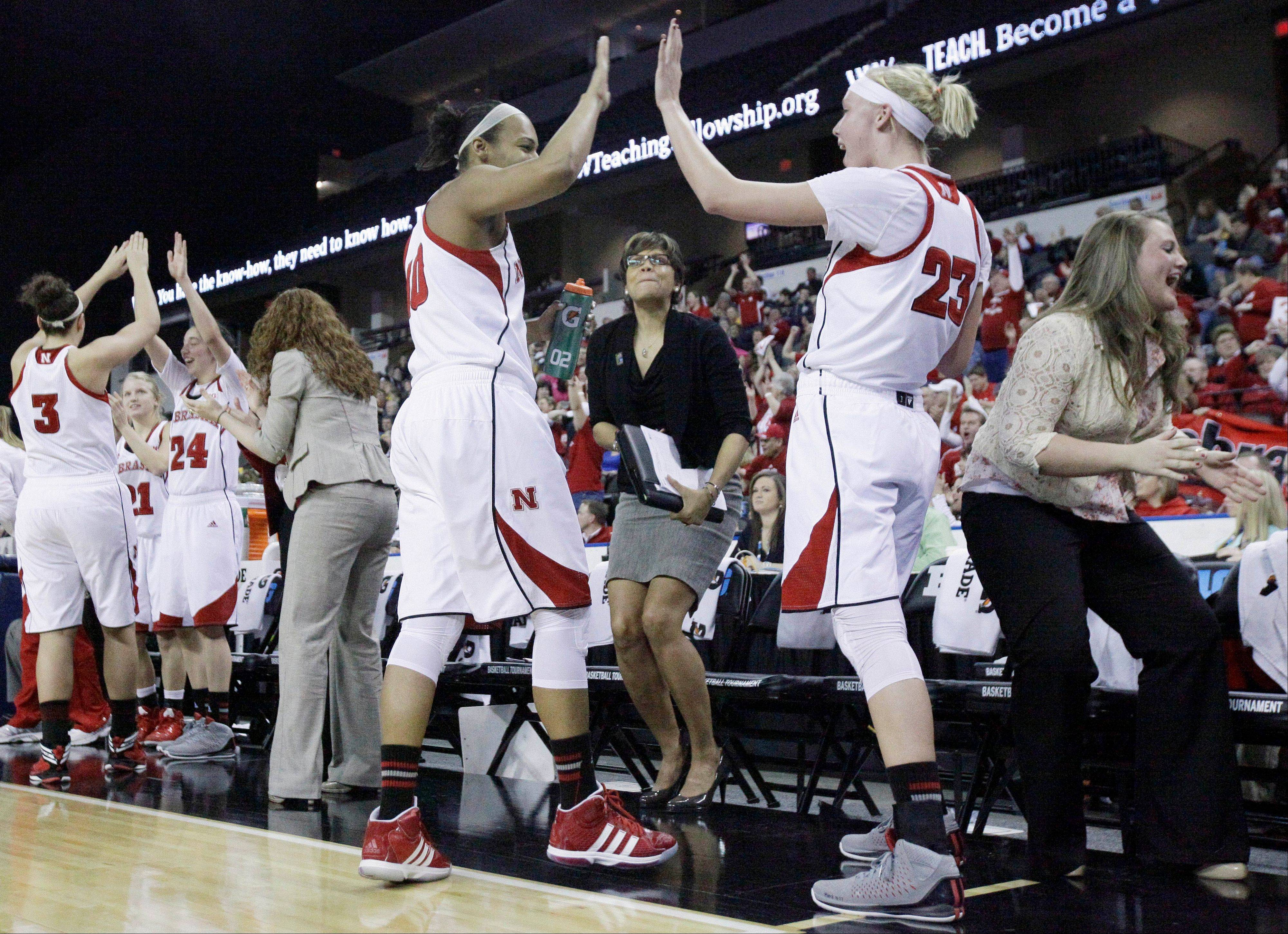 Nebraska players and staff celebrate after guard Brandi Jeffery, not pictured, scored during the second half of an NCAA college basketball game against Iowa in the Big Ten Conference tournament in Hoffman Estates, Ill., on Friday, March 8, 2013. Nebraska won 76-61. (AP Photo/Nam Y. Huh)