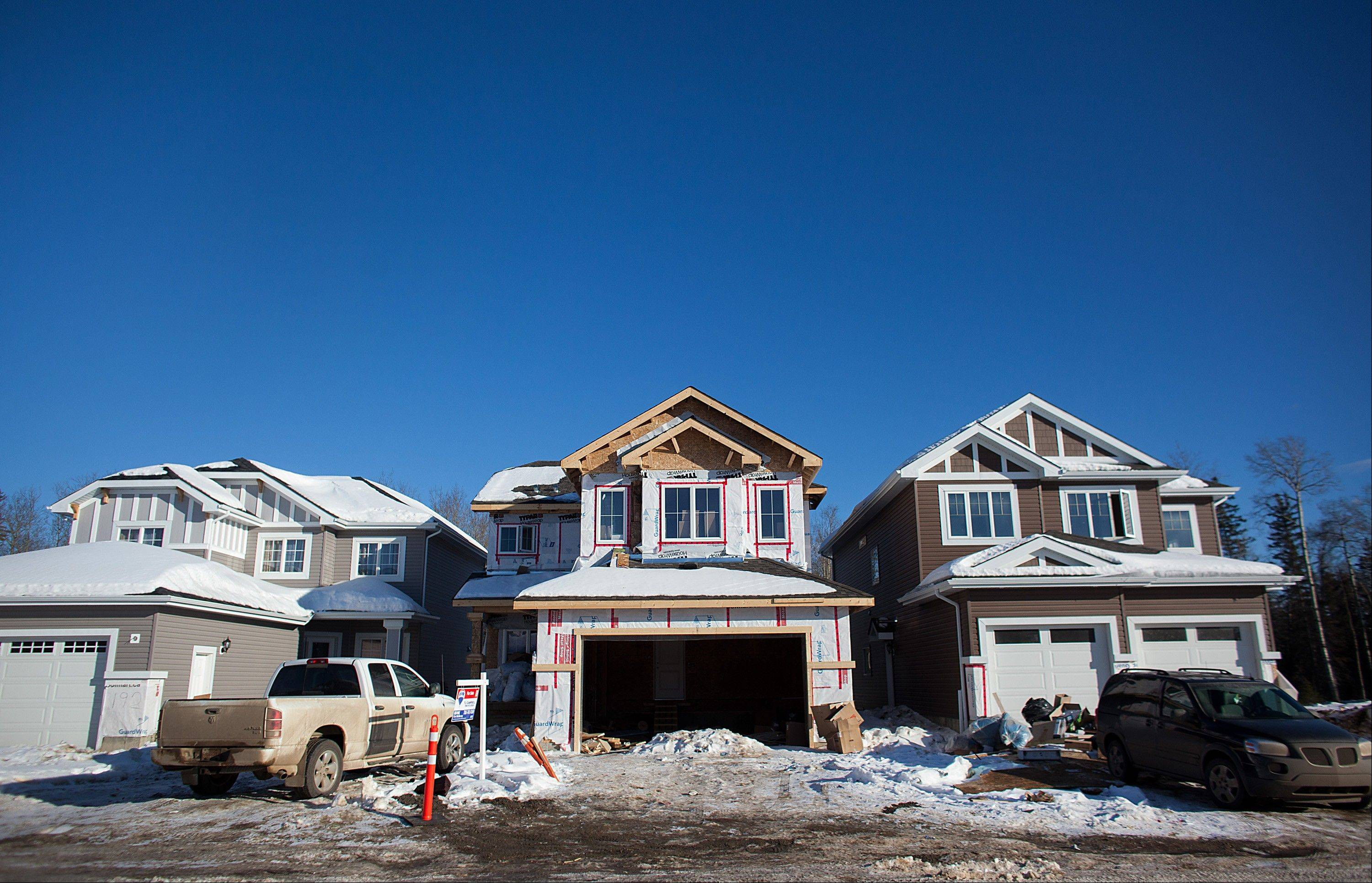 Trucks sit parked Thursday outside of new homes under construction.