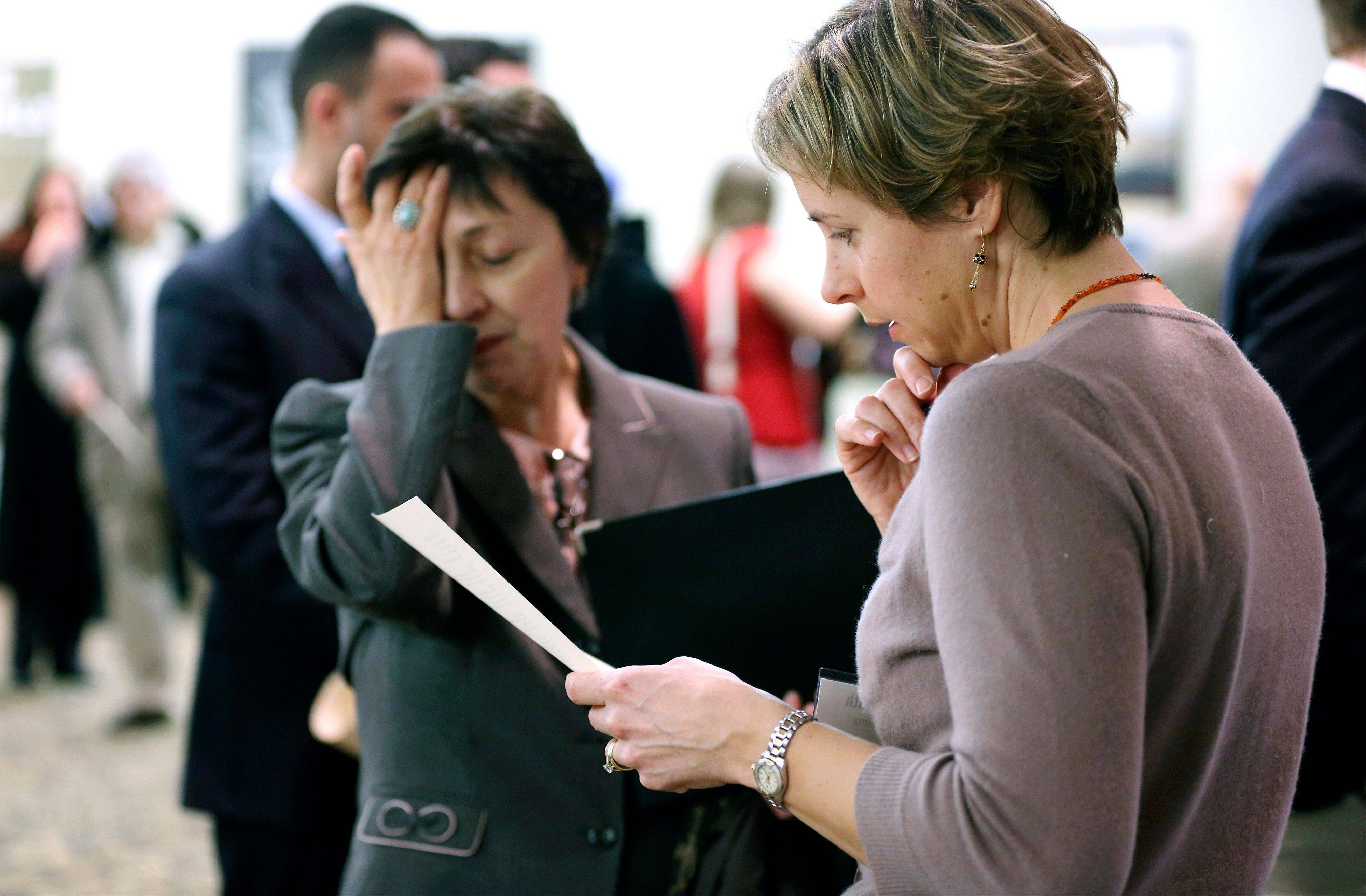 Ann Oganesian, left, of Newton, Mass., pauses as she speaks with a State Dept. employee about job opportunities with the federal government during a job fair in Boston. The Labor Department is scheduled to release the jobs report Friday .