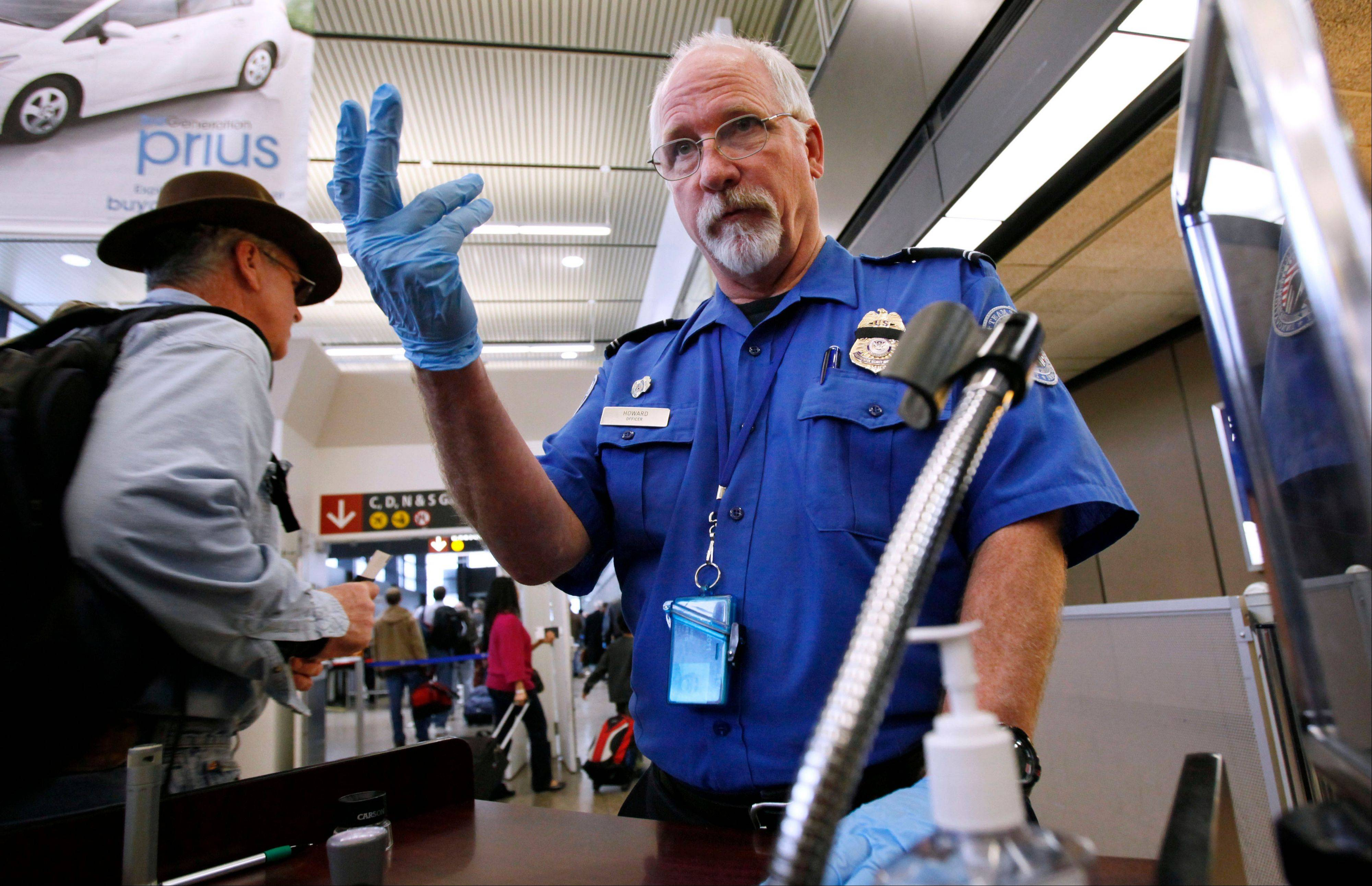 In this Jan. 4, 2010 photo, TSA officer Robert Howard signals an airline passenger forward at a security check-point at Seattle-Tacoma International Airport in SeaTac, Wash. Flight attendants, pilots, federal air marshals and even insurance companies are part of a growing backlash to the Transportation Security Administrationís new policy allowing passengers to carry small knives and sports equipment like souvenir baseball bats and golf clubs onto planes.