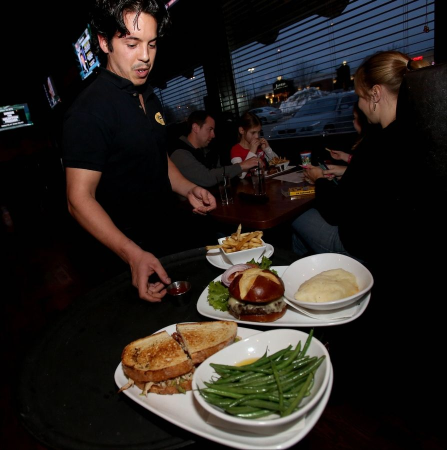 Nate Galan serves lunch patrons hearty sandwiches at the Spotted Fox Ale House in St. Charles.