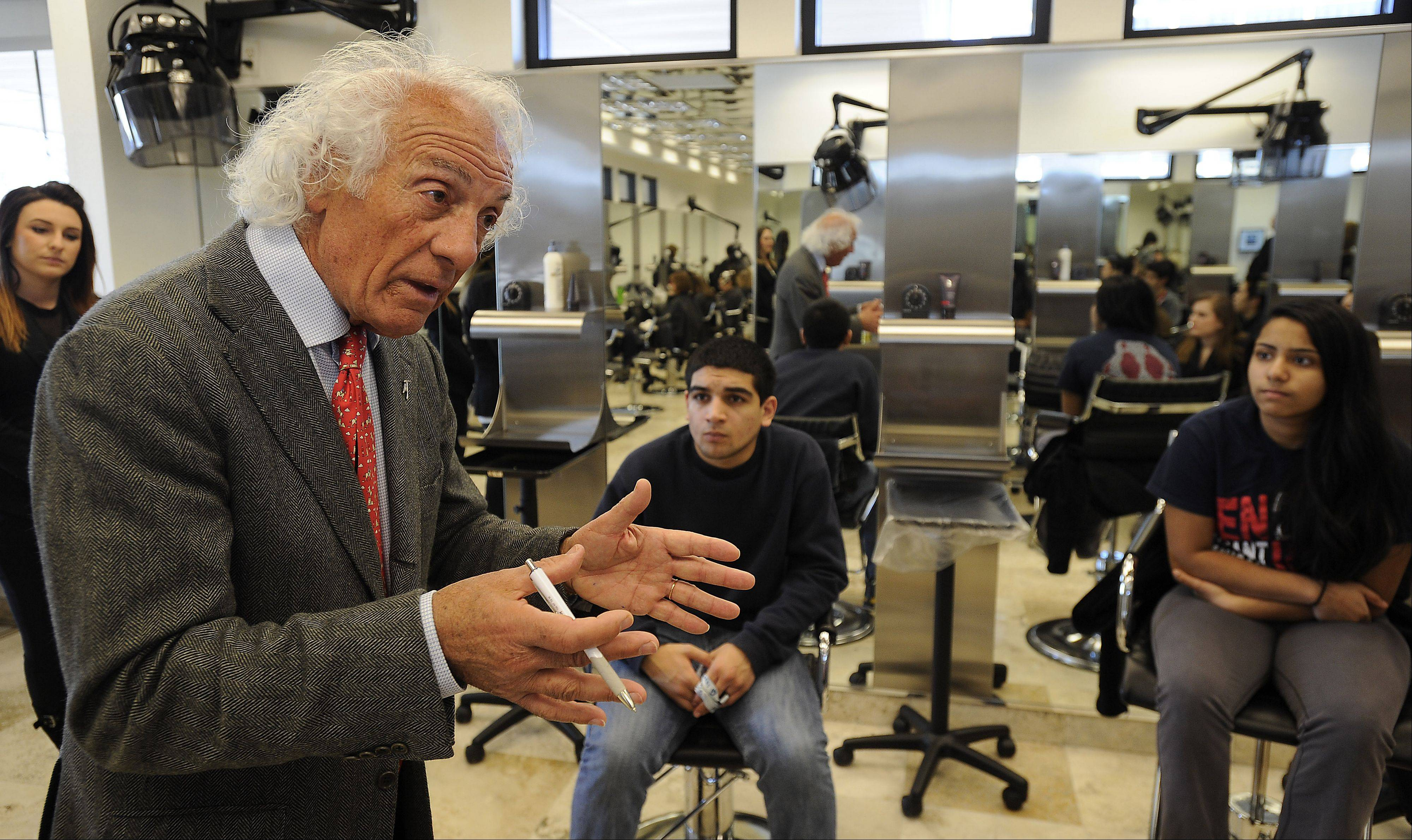 High school students greet Mario Tricoci in Schaumburg on Wednesday. Tricoci was at his salon speaking to the Young Entrepreneurs Academy participants. The program teaches students about entrepreneurship and professional presence.