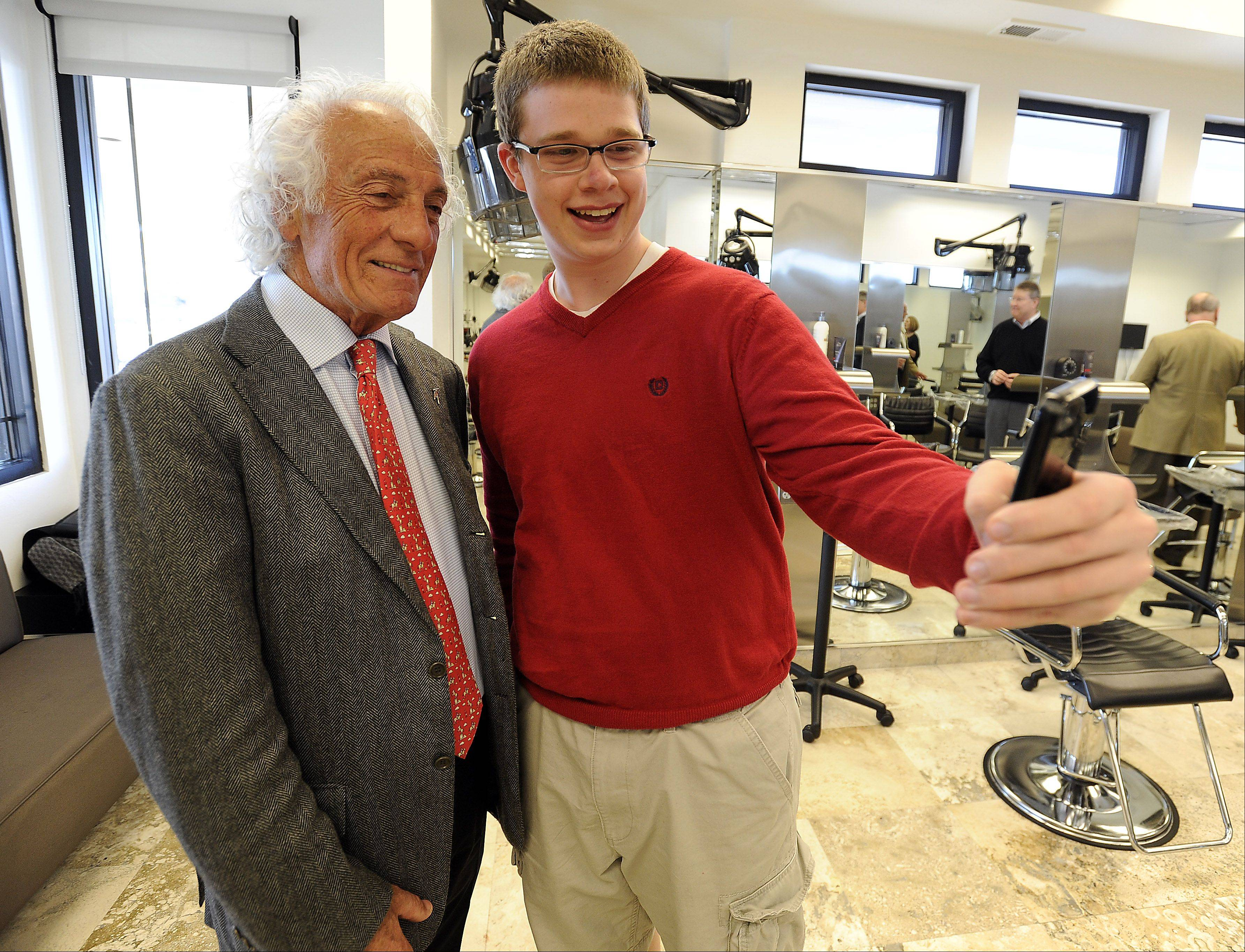 Conant High School student Ben Kusswurm, 17, takes advantage of the moment to take a picture of himself and Mario Tricoci in Schaumburg on Wednesday. Kusswurm is part of the Young Entrepreneurs Academy, which teaches students about entrepreneurship and professional presence.