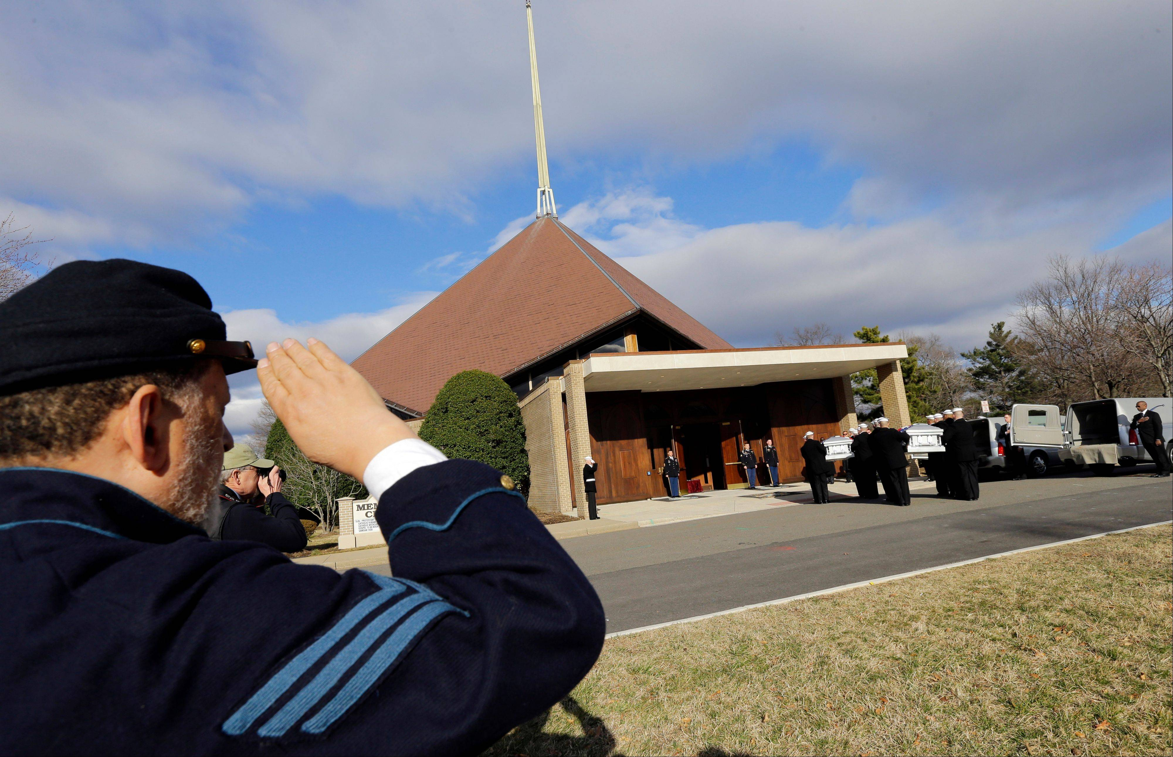 A man in Civil War period attire salutes Friday as two flag draped caskets arrive at Fort Meyer Memorial Chapel for services to honor two sailors from the Civil War ship, the USS Monitor.