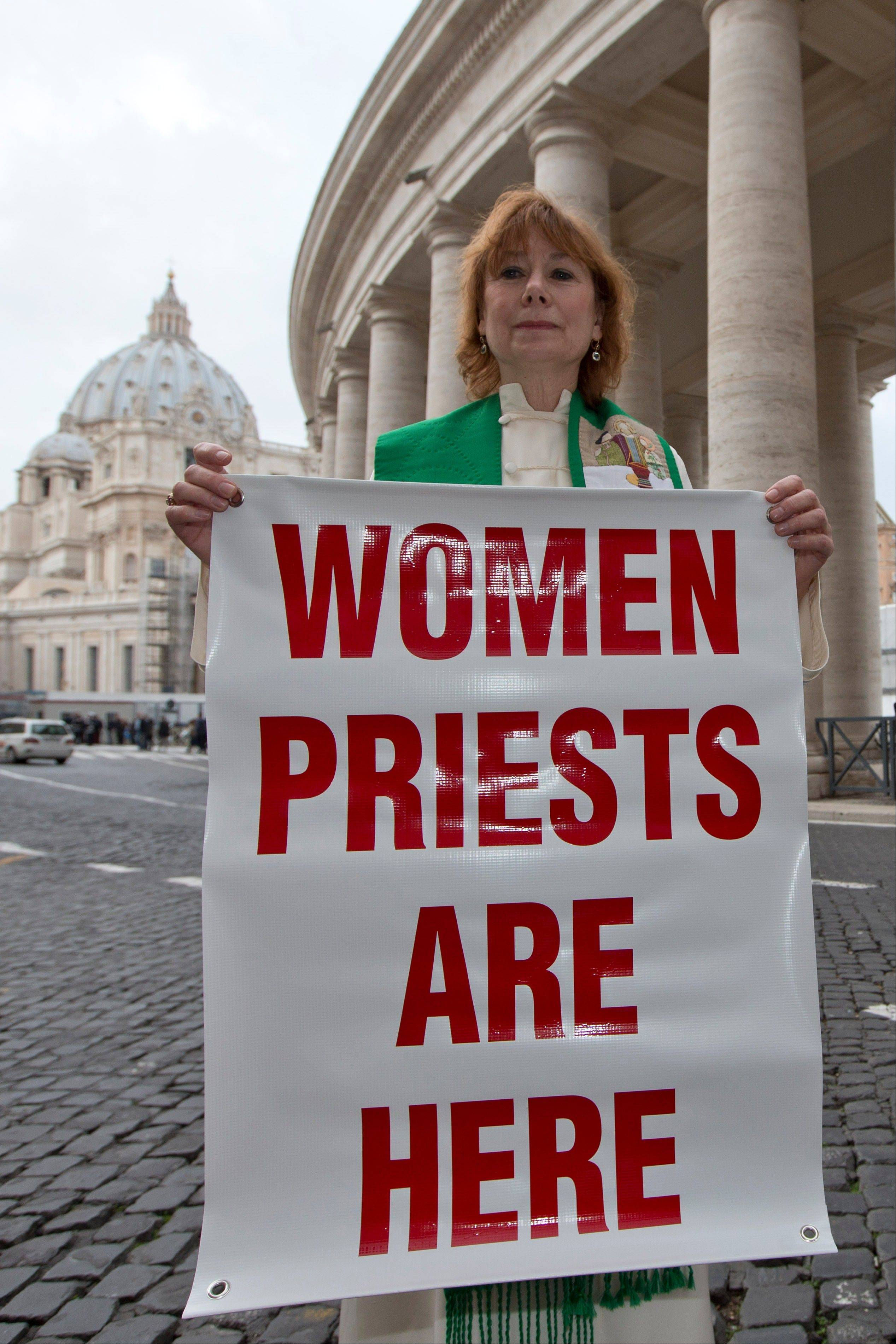 "Janice Sevre-Duszynska poses with a banner at the Vatican. The Vatican has made the illicit ordination of women one of the ""gravest"" canonical crimes. The sanction is swift and severe: automatic excommunication for the woman receiving the attempted ordination and the priest who performs the ceremony."