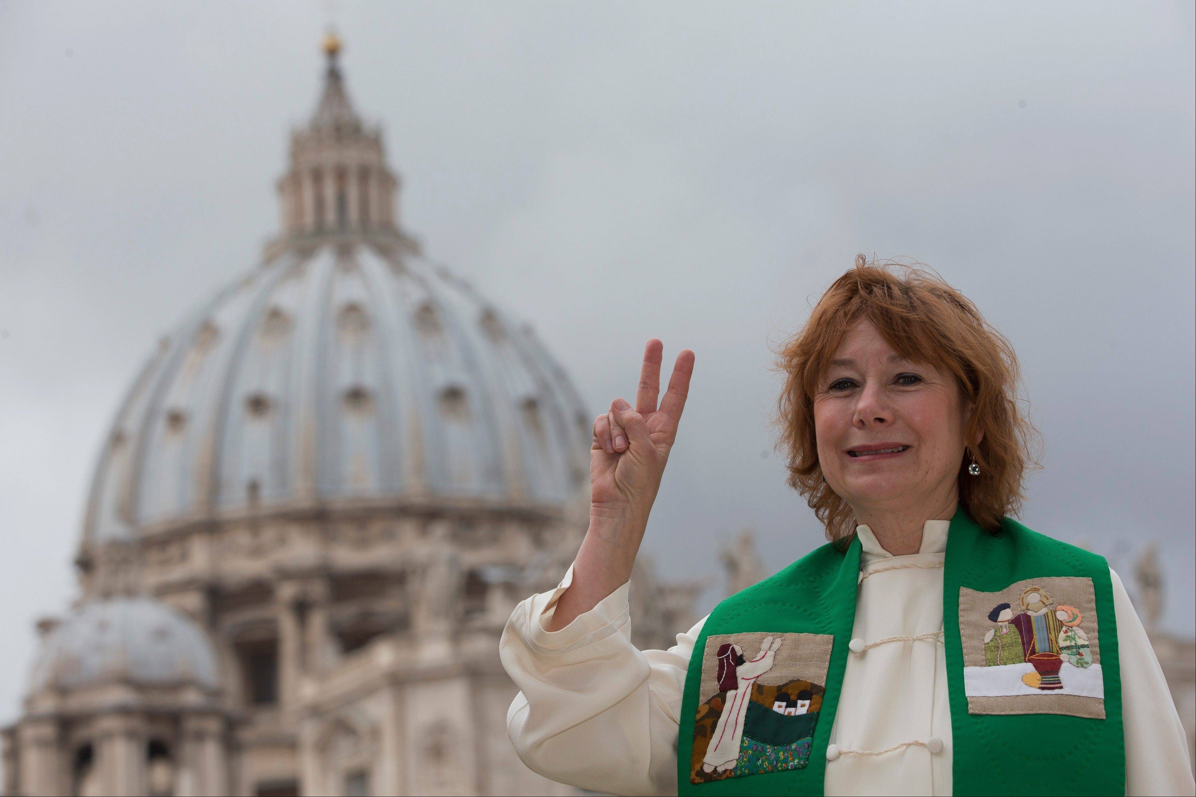 "Janice Sevre-Duszynska poses as the dome of St. Peter's Basilica is seen in background, in Rome. Supporters of the female priest movement argue that Jesus called ""women and men to be disciples and equals living the Gospel."""