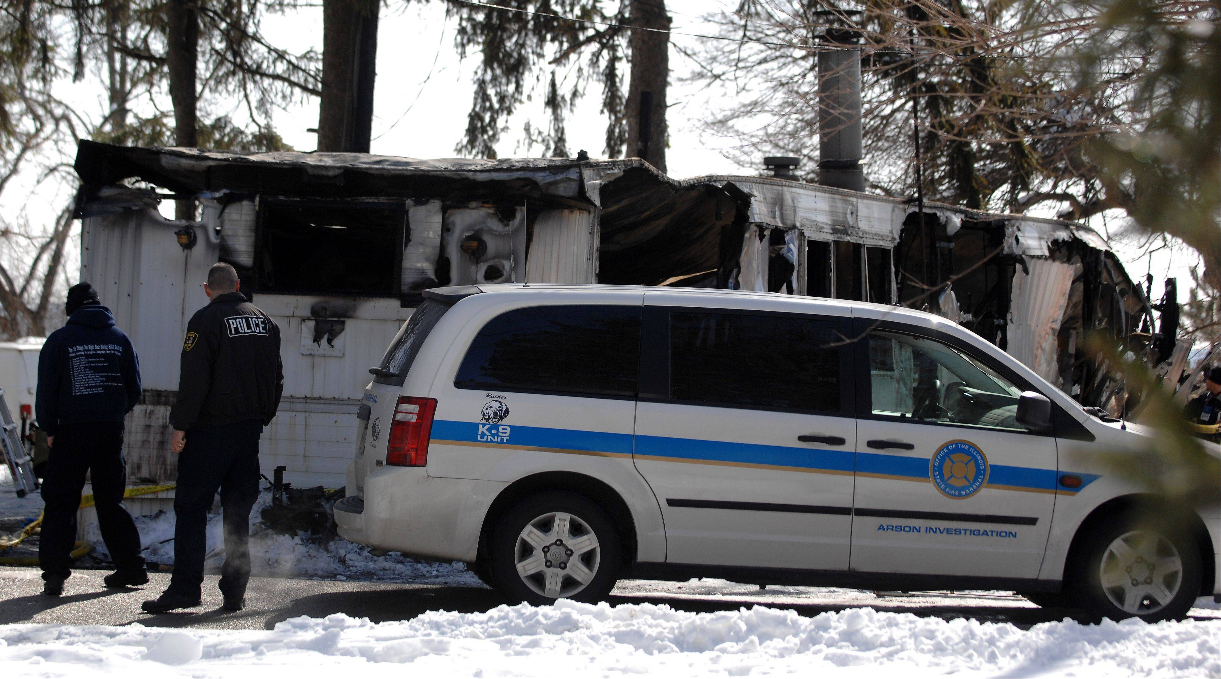 Police and arson investigators check out the scene of a fire Friday morning in a mobile home park on South McLean Boulevard in Elgin.