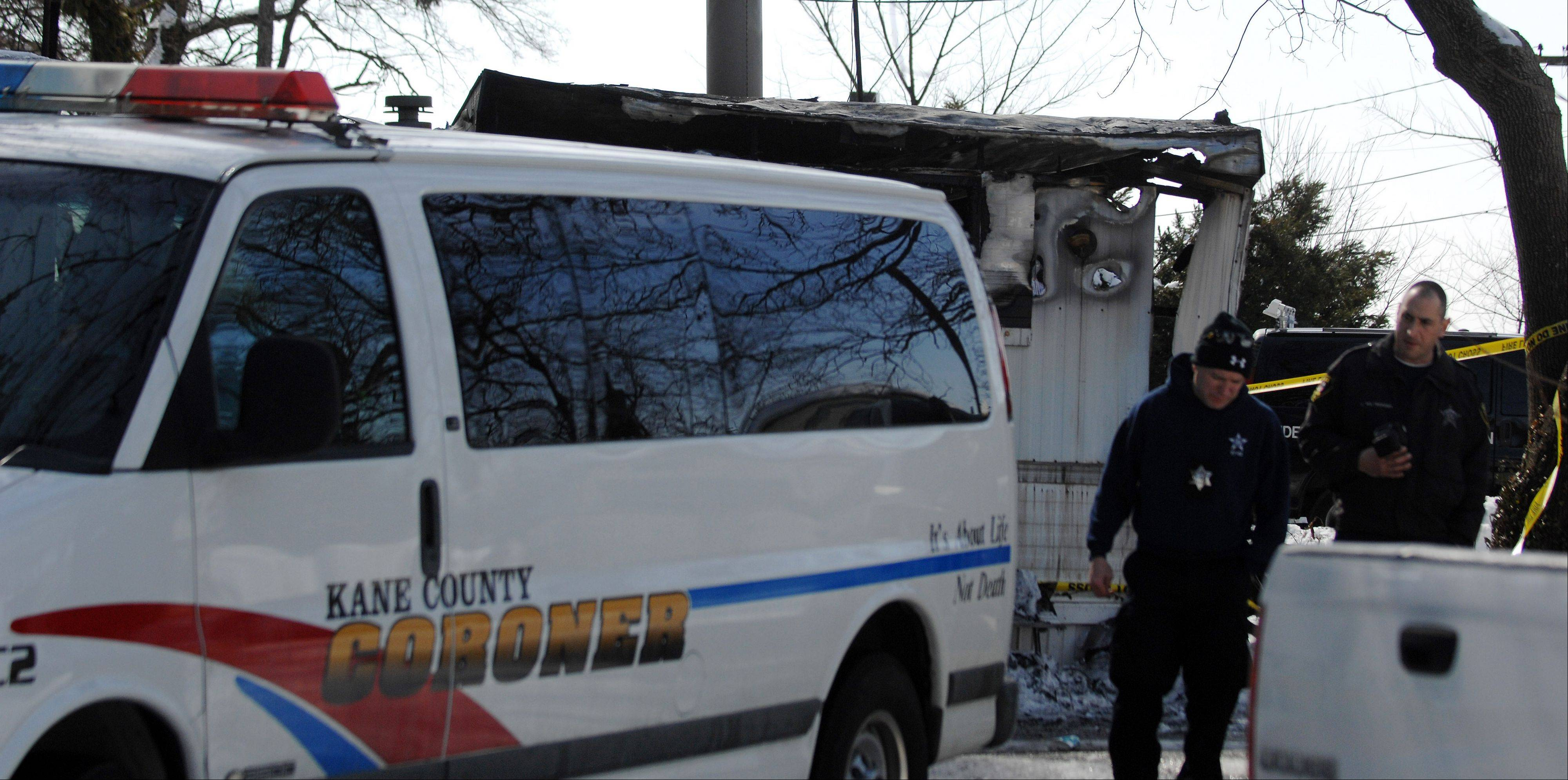 The coroner prepares to leave the scene of a fire Friday in a mobile home park on McLean Boulevard in Elgin. A 36-year-old man was found dead in the home that burned.