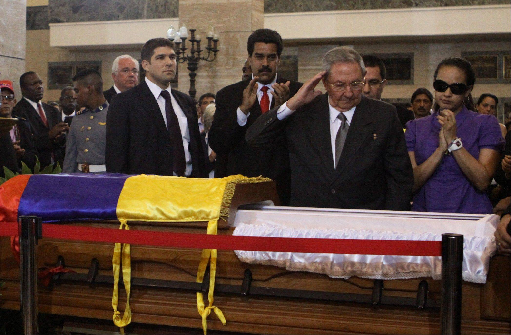 Cuba's President Raul Castro salutes as he stands next to the coffin containing the body of Venezuela's late President Hugo Chavez. A state funeral for Chavez attended by some 33 heads of government is scheduled to begin Friday morning. At right is Chavez's daughter Rosa Virginia Chavez and center is Vice-President Nicolas Maduro.