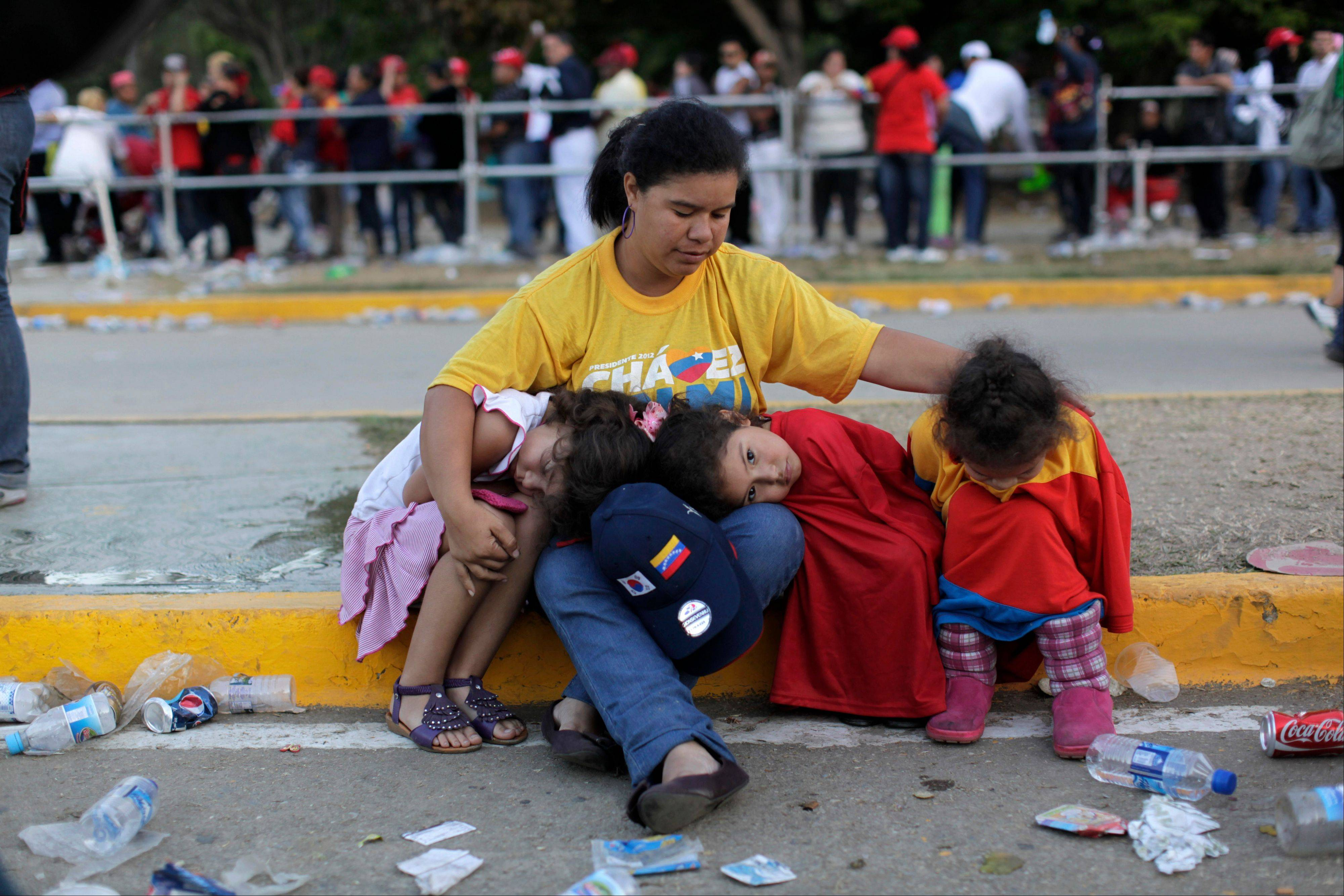 A woman sits with three girls outside the military academy where a funeral ceremony will take place for Venezuela's late President Hugo Chavez in Caracas, Venezuela, Friday, March 8, 2013.