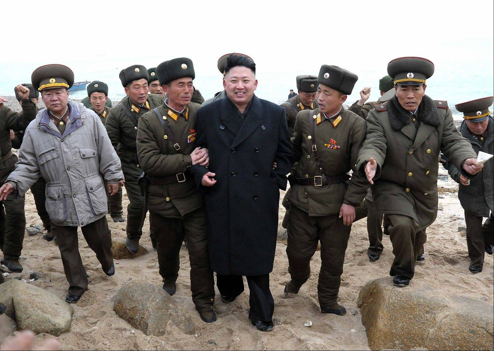 North Korean leader Kim Jong Un, center, walks with military personnel as he arrives for a military unit on Mu Islet, located in the southernmost part of the southwestern sector of North Korea's border with South Korea.