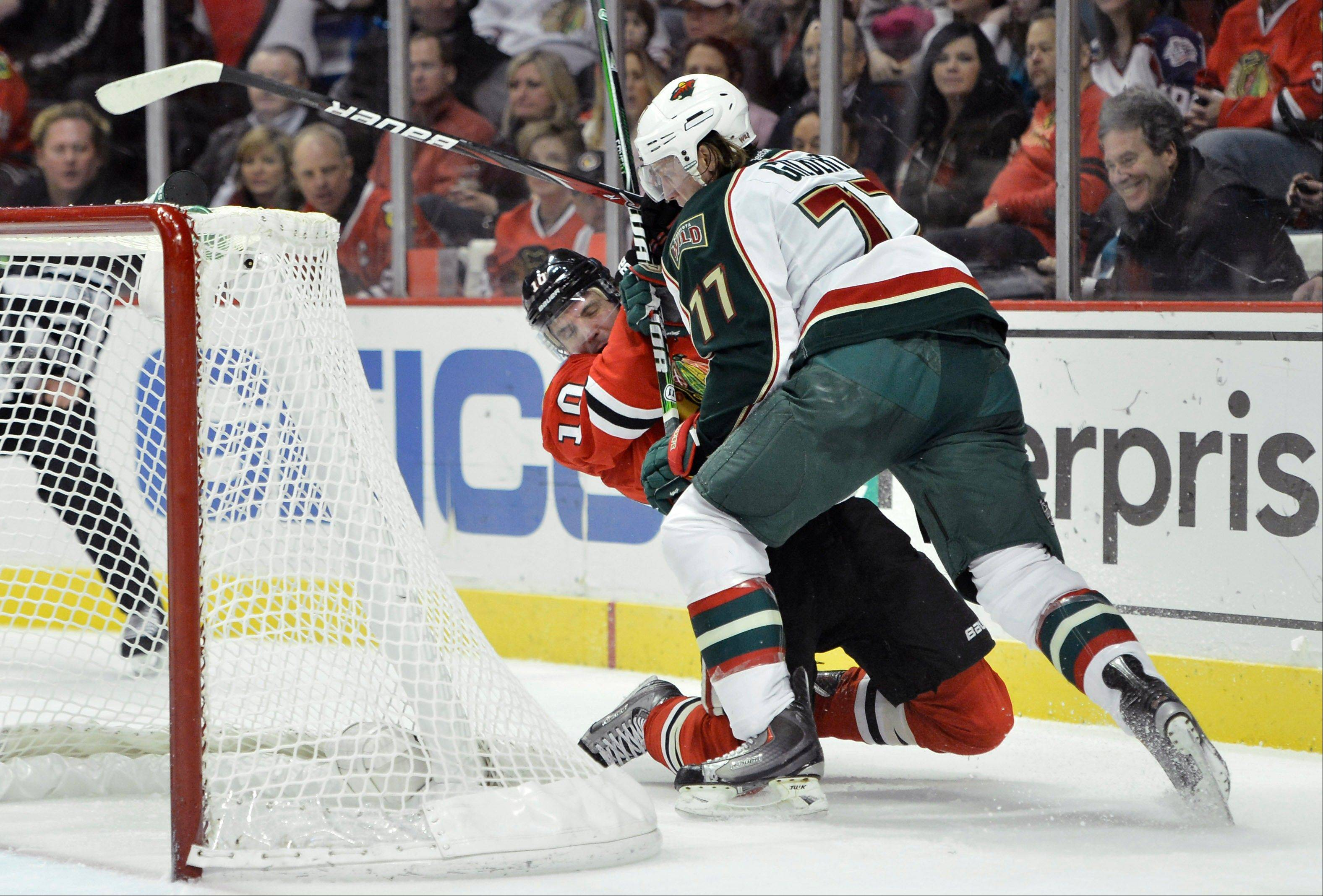 Minnesota Wild defenseman Tom Gilbert, right, takes down Blackhawks left wing Patrick Sharp during the second period of Tuesday night's game. Now the rumor is Sharp could be out for three weeks.