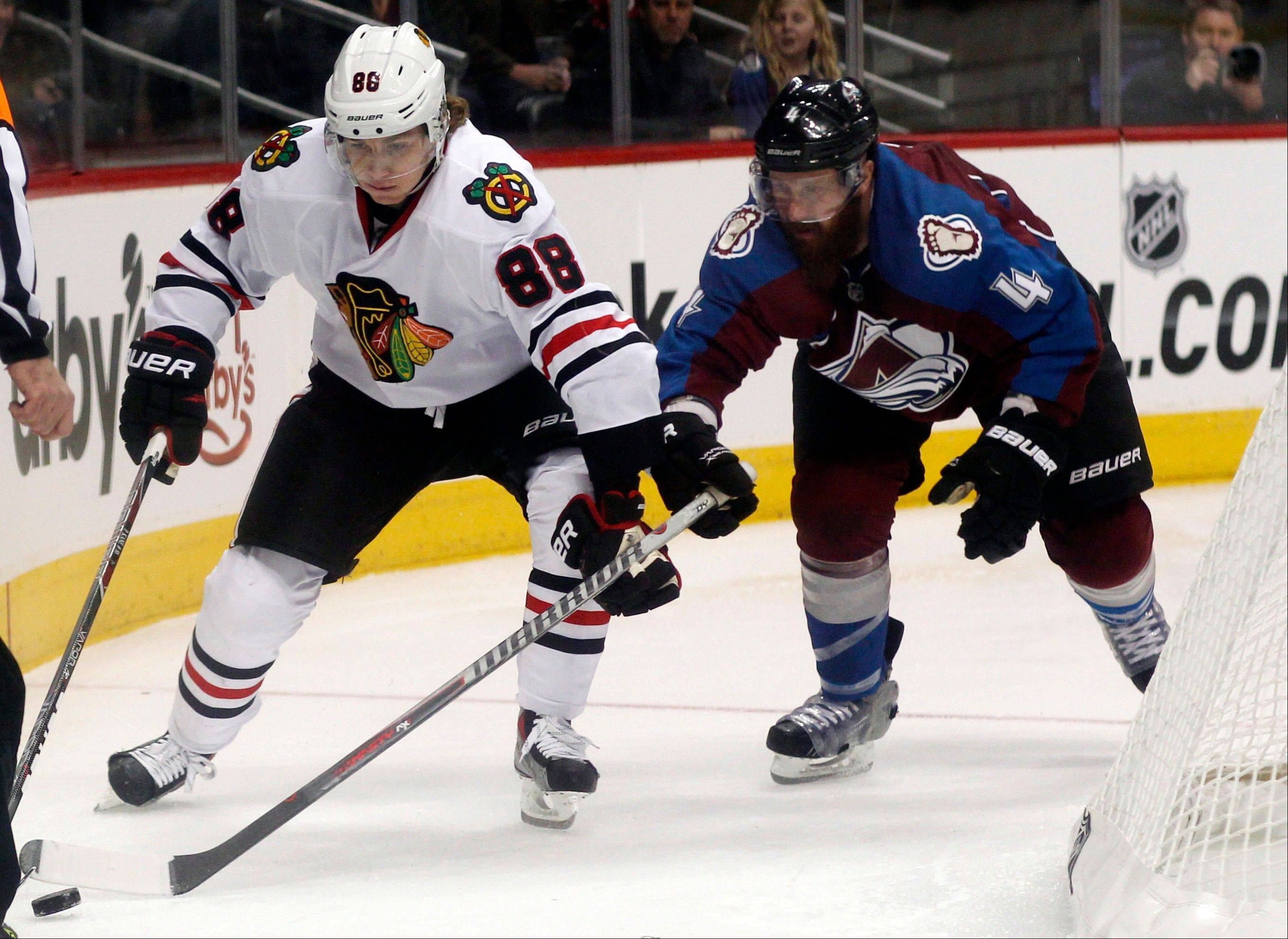 Chicago Blackhawks right wing Patrick Kane, left, works the puck behind the net as Colorado Avalanche defenseman Greg Zanon covers in the second period.