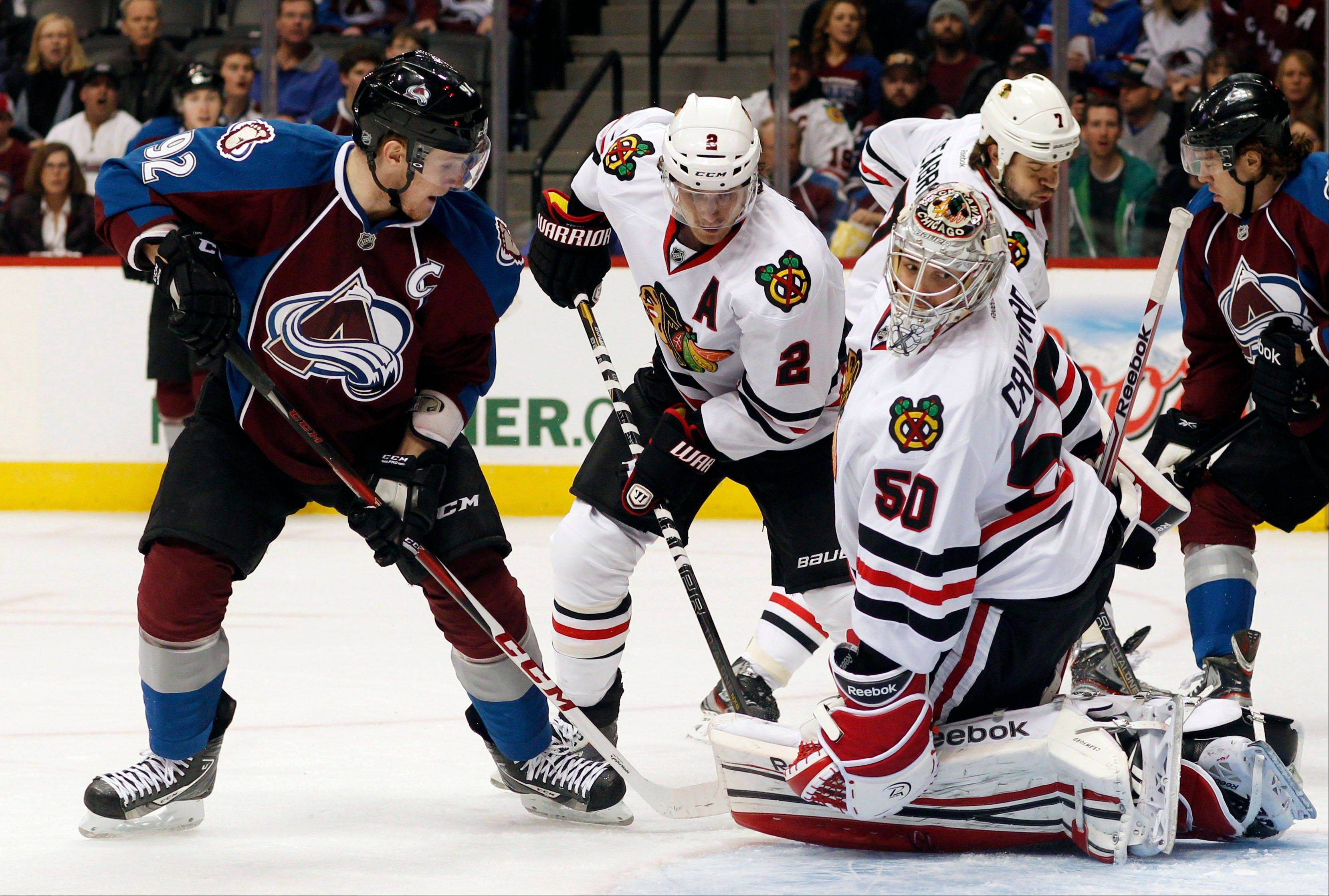 Colorado Avalanche left wing Gabriel Landeskog, left, of Sweden, directs a shot at Chicago Blackhawks goalie Corey Crawford, right, as defenseman Duncan Keith looks on in the first period.