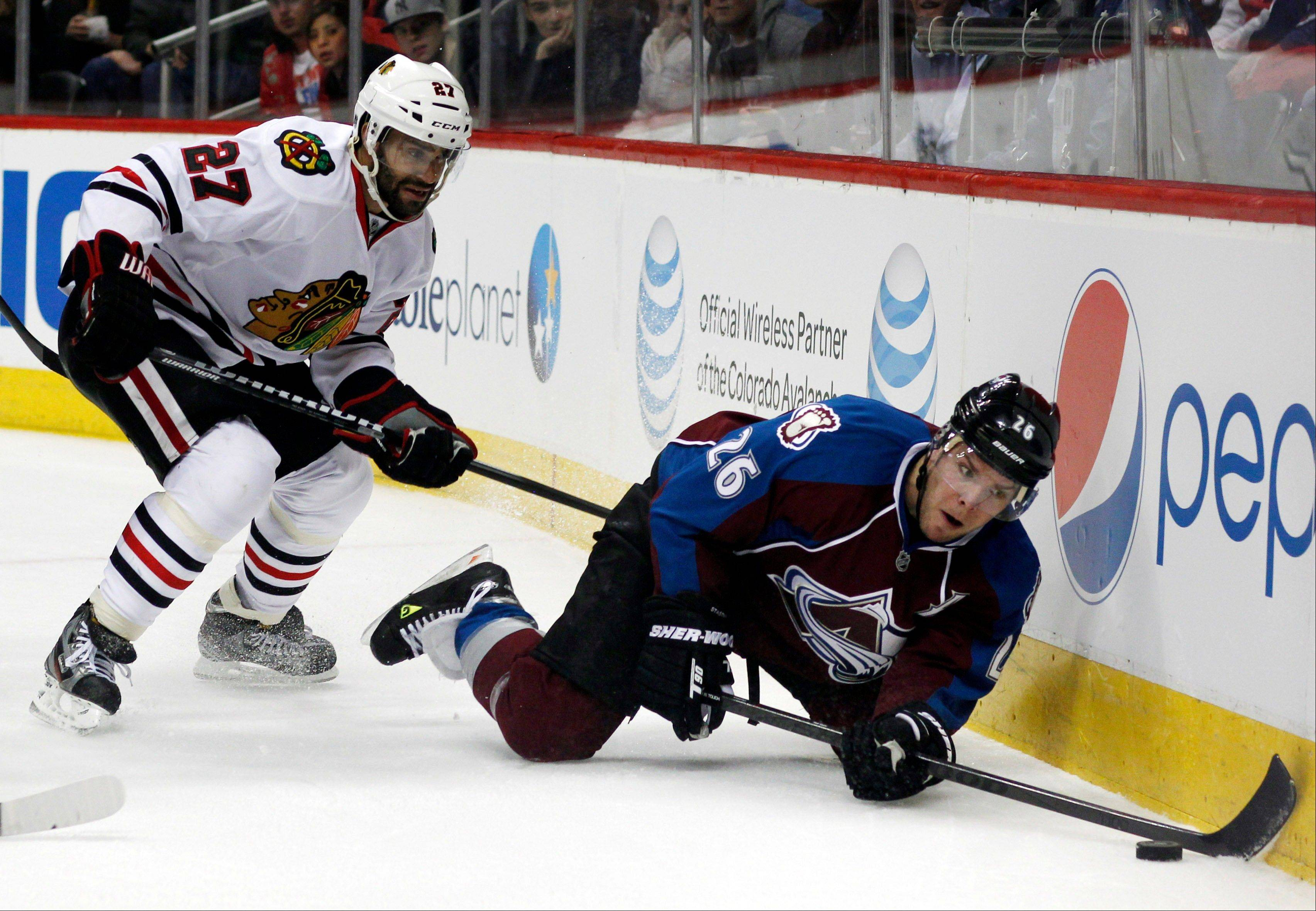 Colorado Avalanche center Paul Stastny, right, reaches out for a loose puck as Chicago Blackhawks defenseman Johnny Oduya covers in the first period.