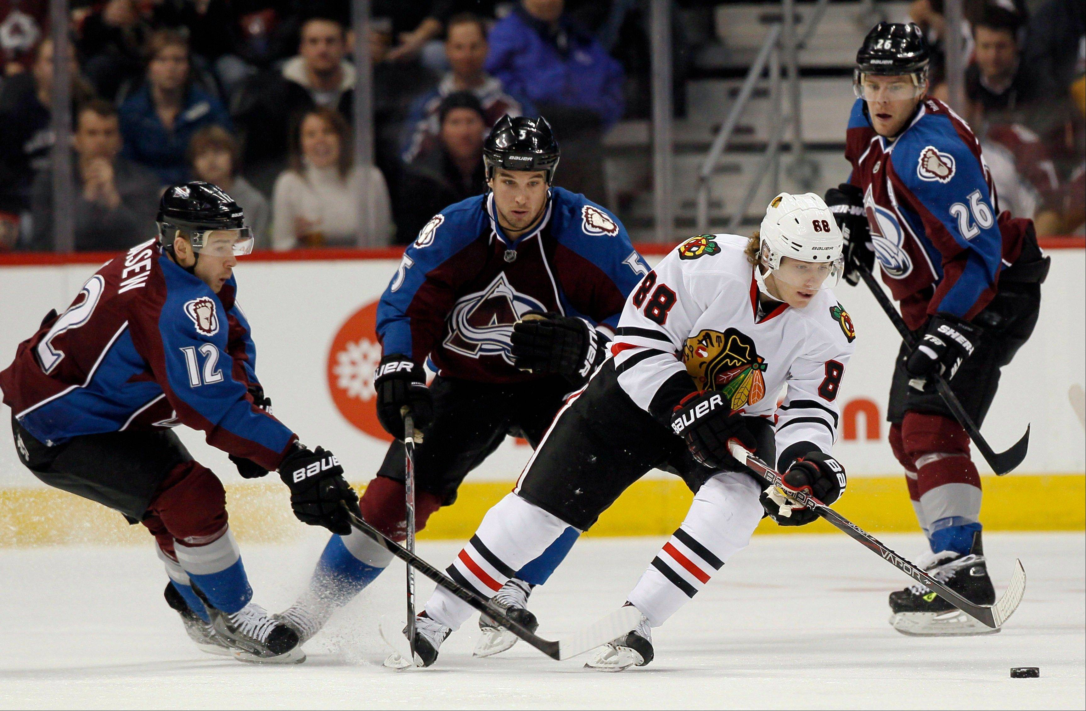 Chicago Blackhawks right wing Patrick Kane, third from left, picks up a loose puck as Colorado Avalanche right wing Chuck Kobasew, far left, defenseman Shane O'Brien, second from left, and center Paul Stastny cover in the first period.