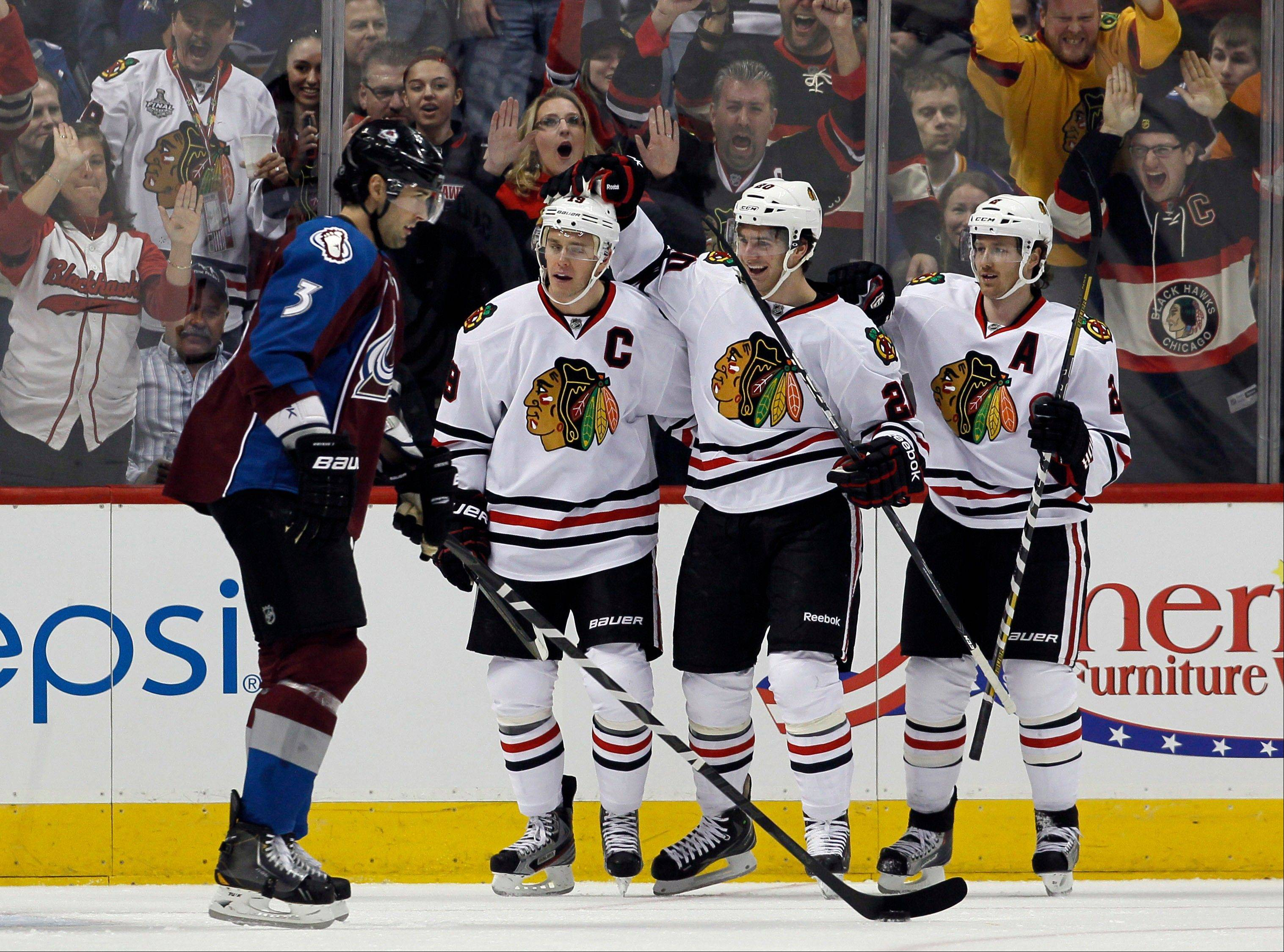 As Colorado Avalanche defenseman Ryan O'Byrne, left, looks on, Chicago Blackhawks center Jonathan Toews, second from left, is congratulated after scoring a goal by teammates Brandon Saad, third from left, and Duncan Keith in the first period.