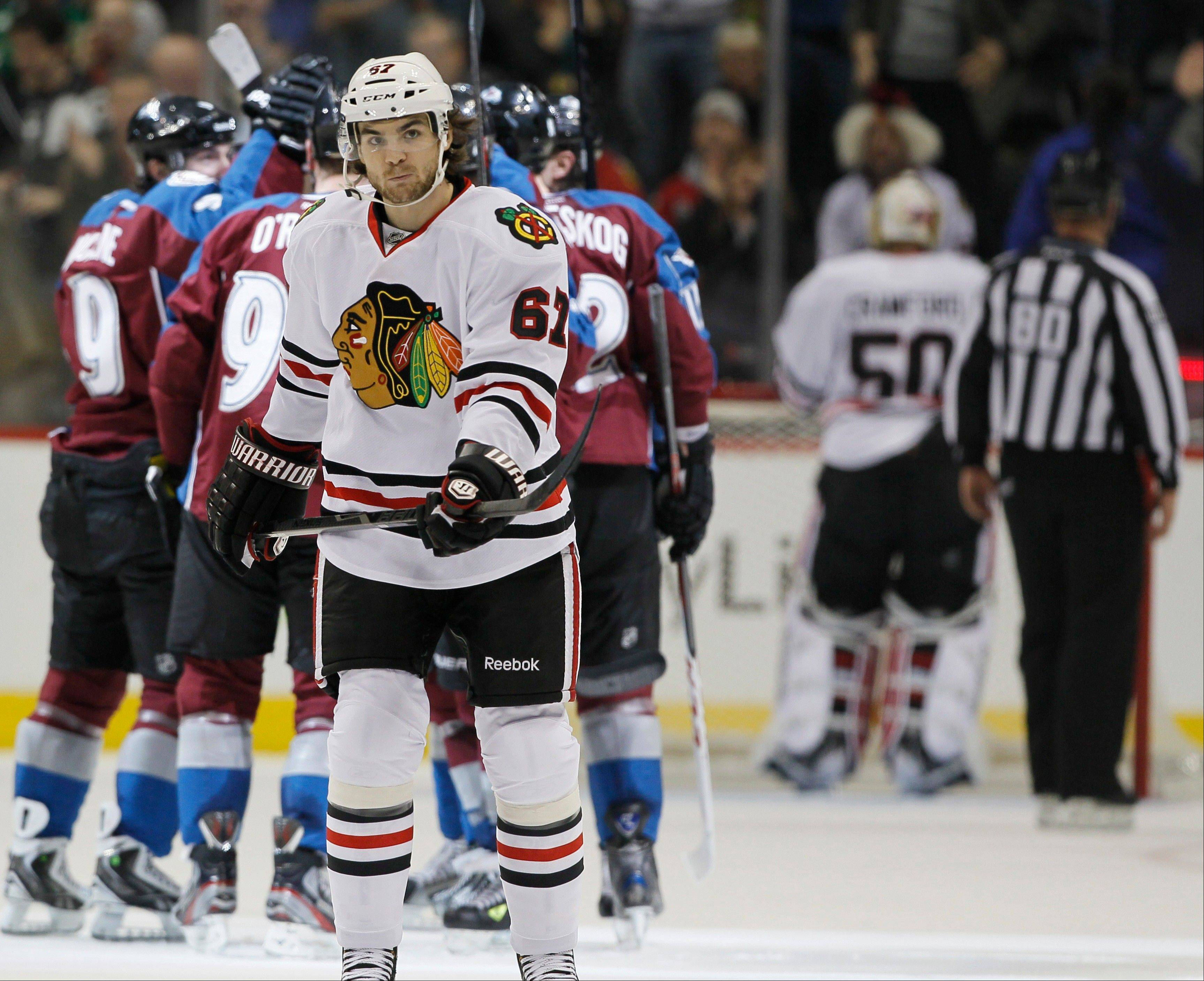 As members of the Colorado Avalanche, back, celebrate a goal by Ryan O'Reilly, Chicago Blackhawks right wing Michael Frolik (67), of the Czech Republic, skates back to the bench in the second period of an NHL hockey game in Denver, Friday, March 8, 2013.
