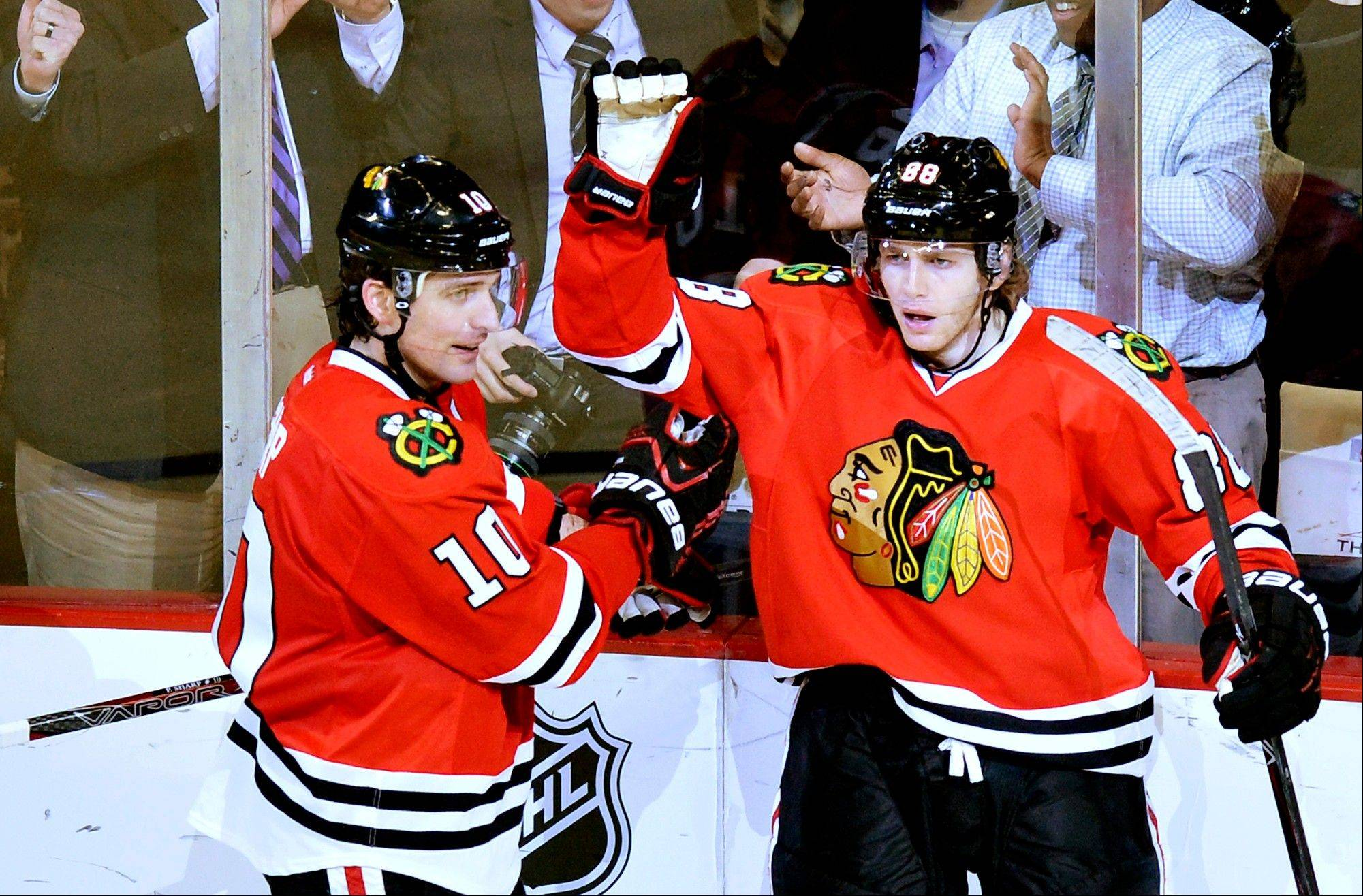 Patrick Sharp, left, and right wing Patrick Kane celebrate Kane's goal Tuesday against Minnesota. Sharp suffered a shoulder injury Wednesday and is out 3-4 weeks.