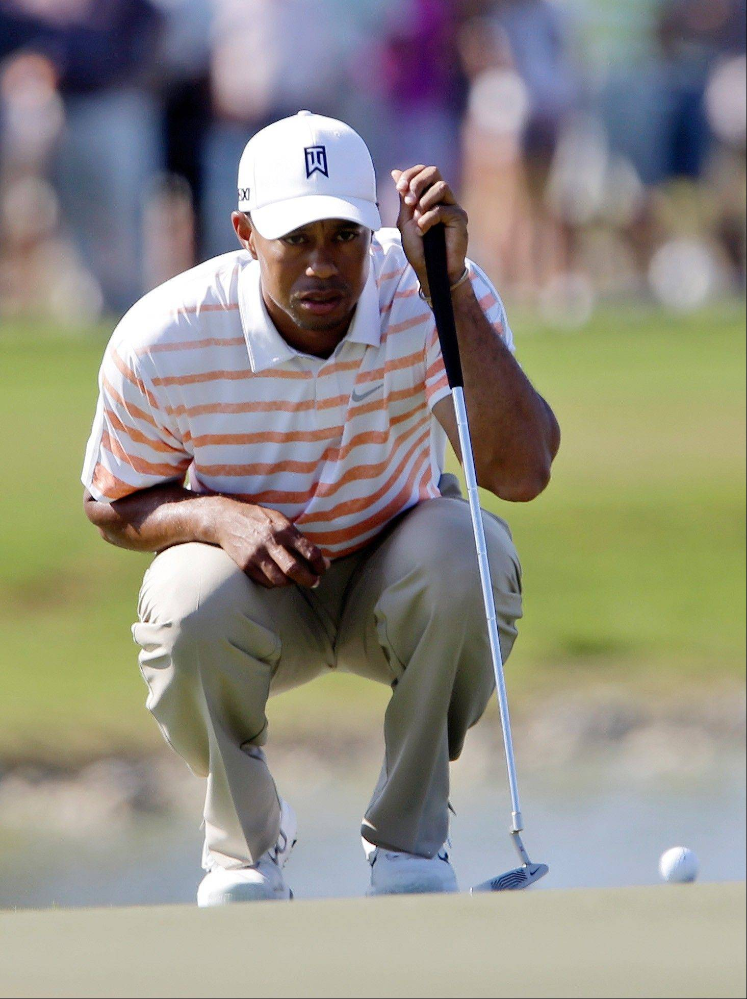 Tiger Woods looks over his putt on the ninth green during the second round of the Cadillac Championship golf tournament Friday, March 8, 2013, in Doral, Fla.