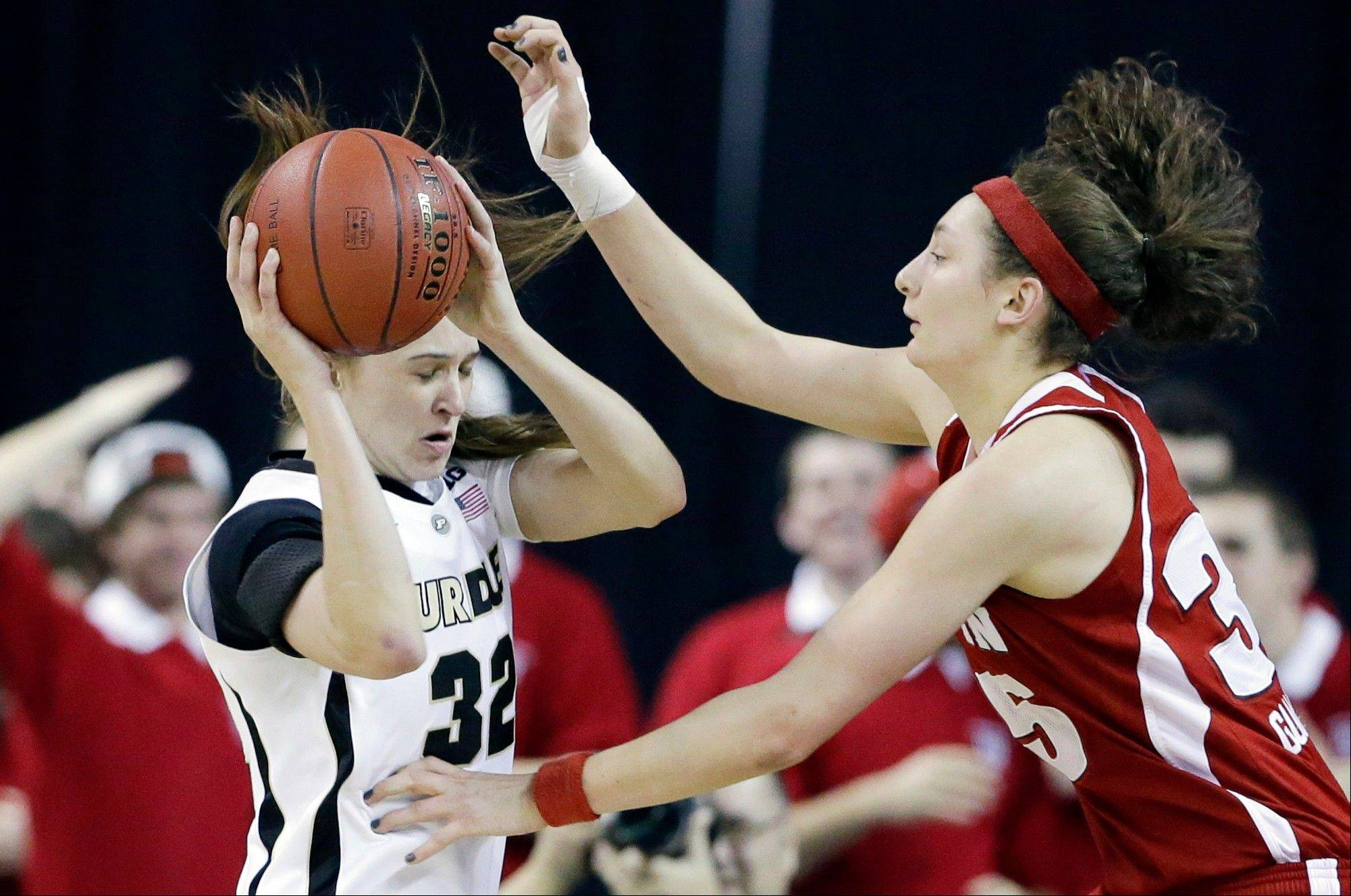 Purdue forward Sam Ostarello, left, looks to a pass as Wisconsin forward Jacki Gulczynski defends during the first half of an NCAA college basketball game in the Big Ten Conference tournament in Hoffman Estates, Ill., on Friday, March 8, 2013. Purdue won 74-62.