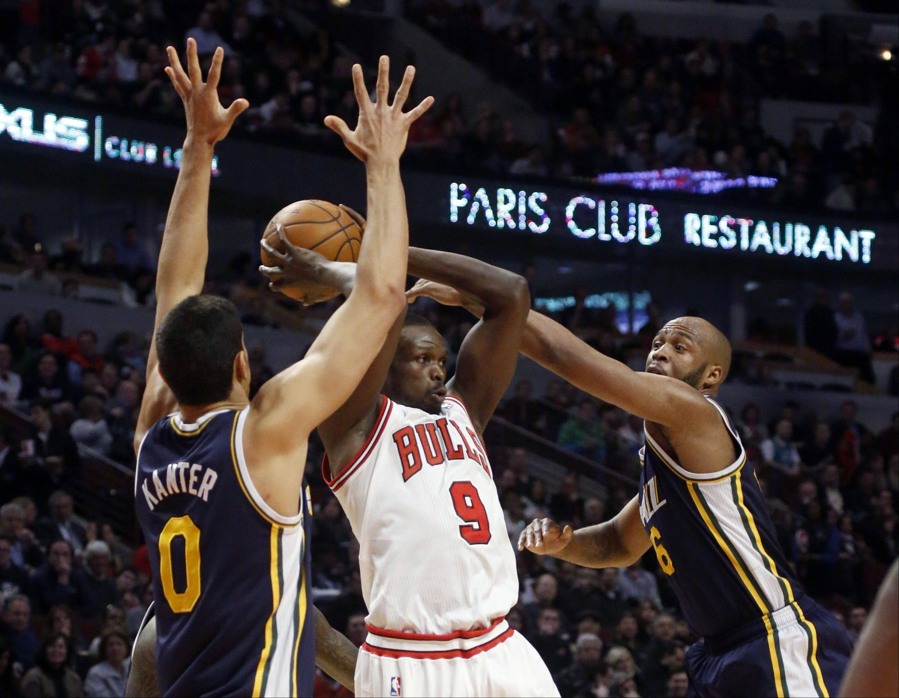 Chicago Bulls forward Luol Deng (9) is pressured by Utah Jazz center Enes Kanter (0) and Jamaal Tinsley (6) during the first half of an NBA basketball game on Friday, March 8, 2013, in Chicago.