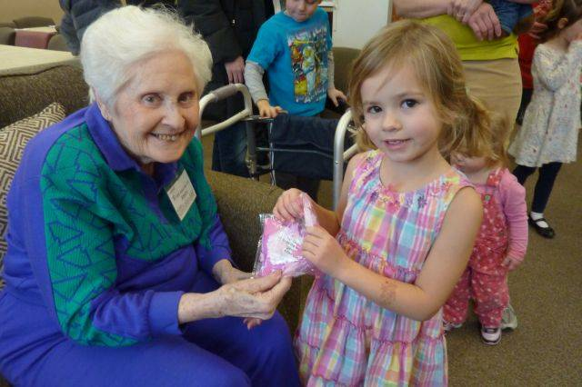 Joyce White gets a special Valentine from Emily Offutt and the St. John Lutheran Church preschoolers who came to visit.