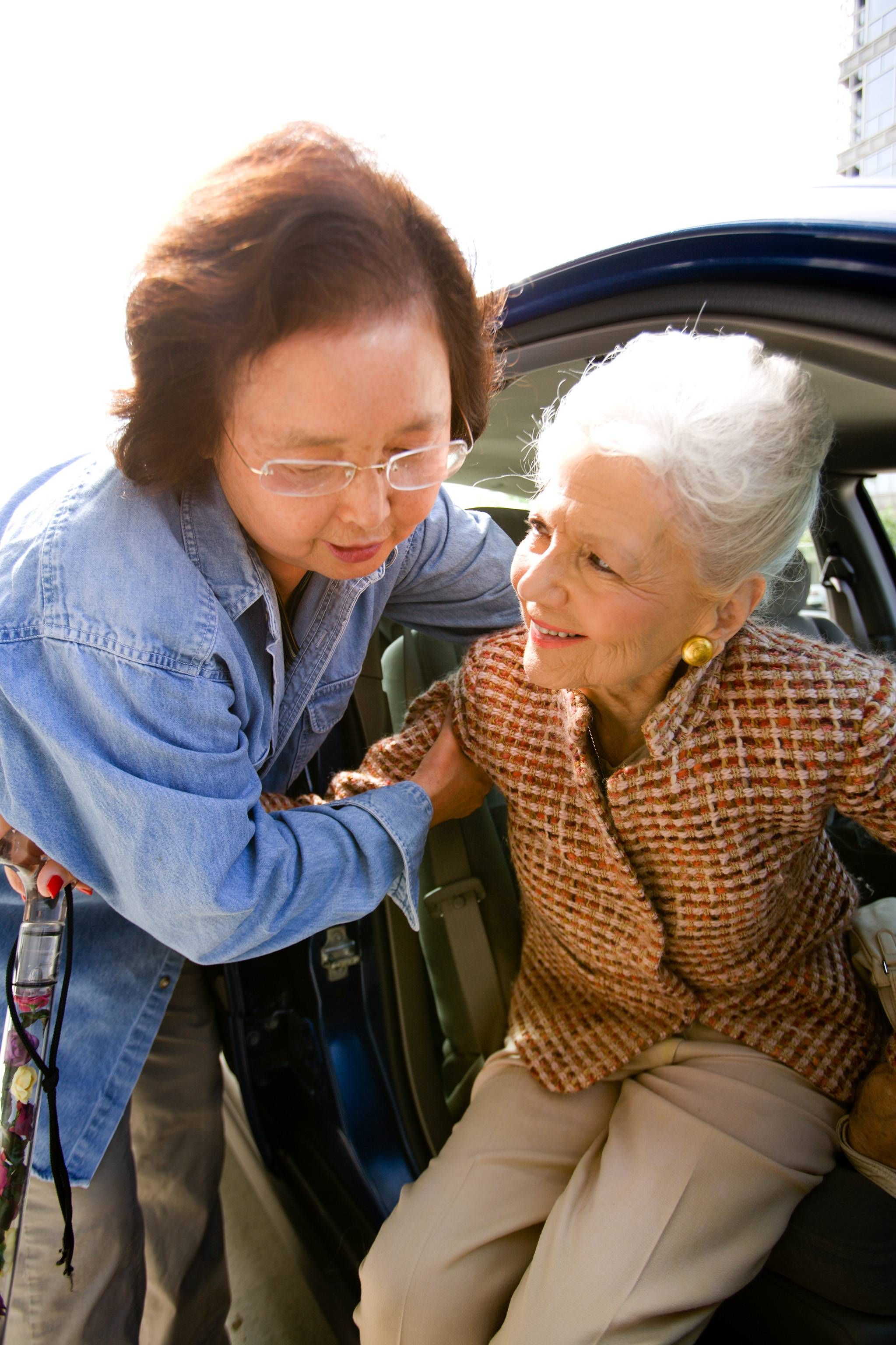 A volunteer helps a cancer patient out of the car after arriving at her appointment location.