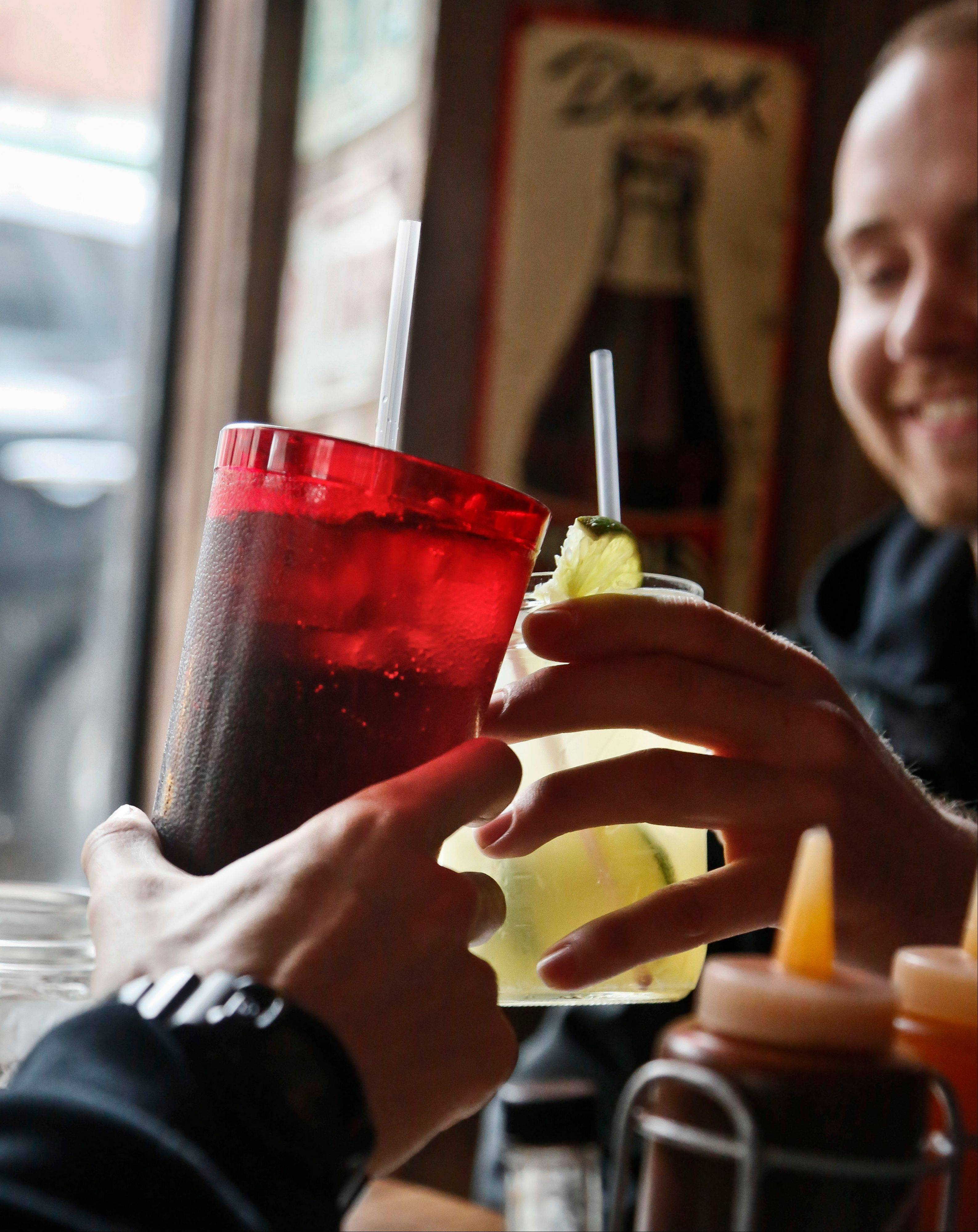 Customers at Brother Jimmy�s BBQ in New York call cheers Friday with 24-ounce and 16-ounce beverages. The nation�s first limit on the size of sugar-laden beverages is set to take effect Tuesday.