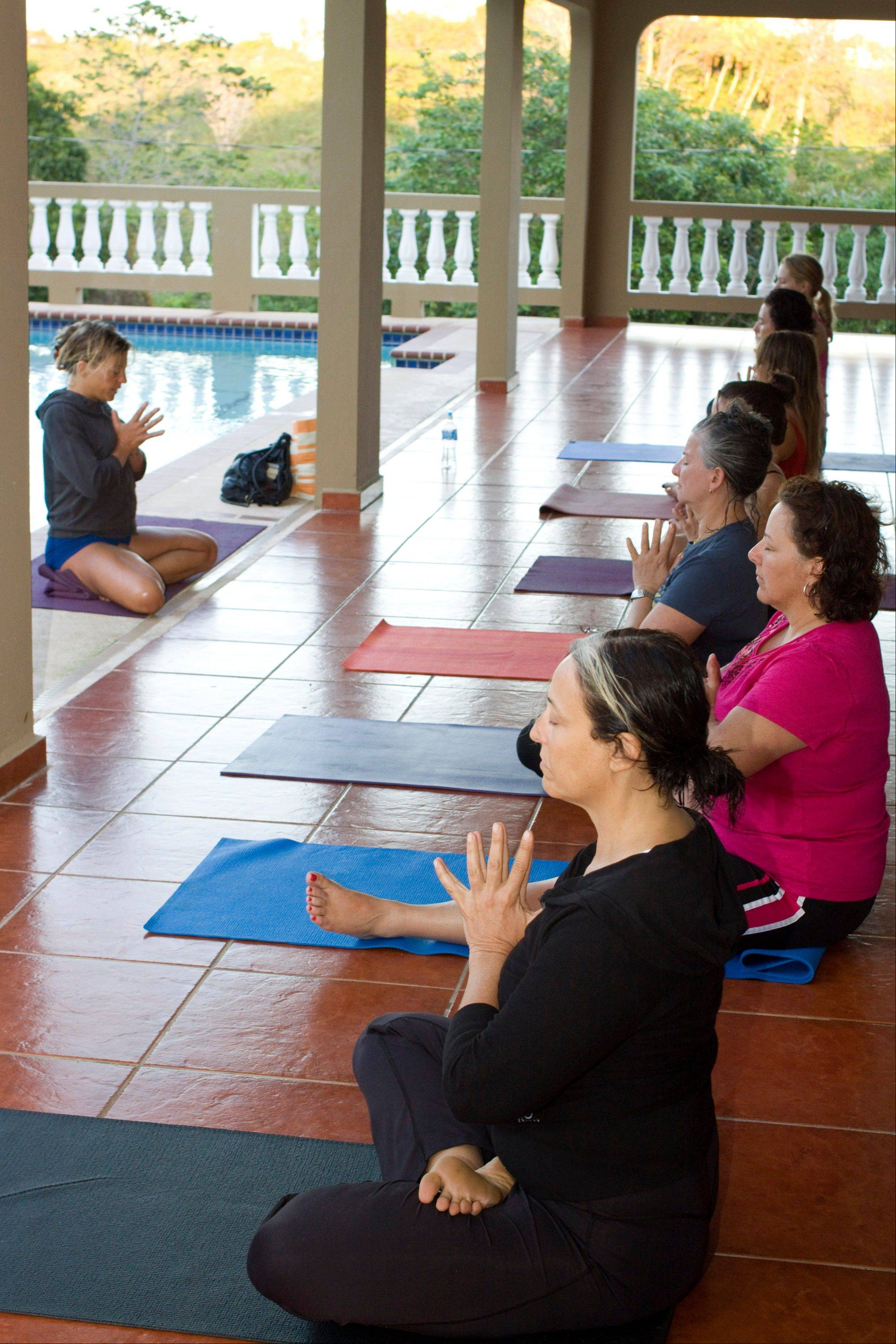 A yoga session in Rincon, Puerto Rico, at a retreat created by Jessica Bellofatto of KamaDeva Yoga and Gina Bradley of Paddle Diva. The program is an example of active vacations tailored to travelers who value healthy lifestyles and new experiences.