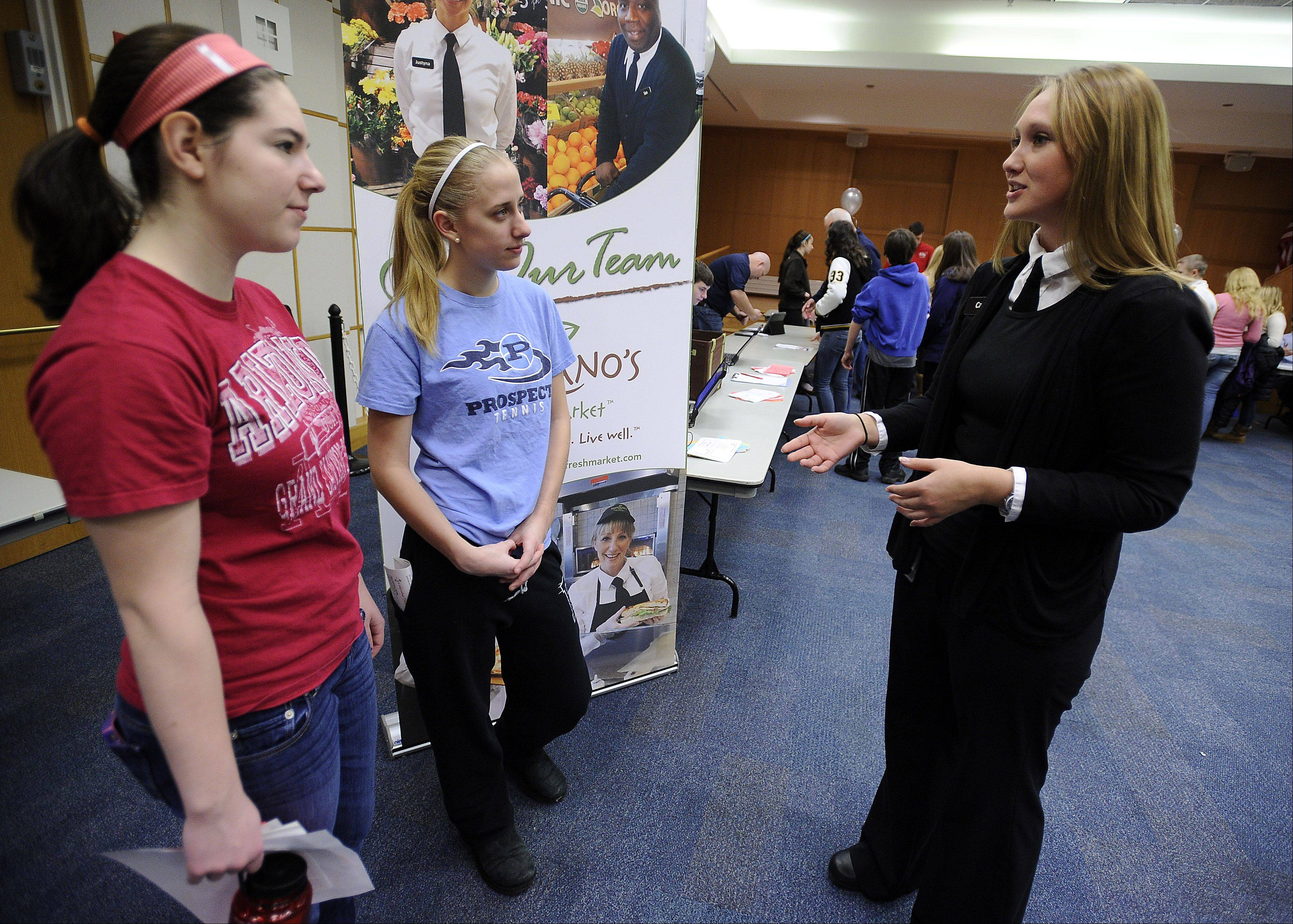 Jessica Hirsh, 16, and her friend Lauren Becherer, 16, both of Prospect High School talk with Cari Henderson of Mariano's grocery in Arlington Heights about summer job prospects at a teen job fair Saturday at the Arlington Heights Memorial Library.