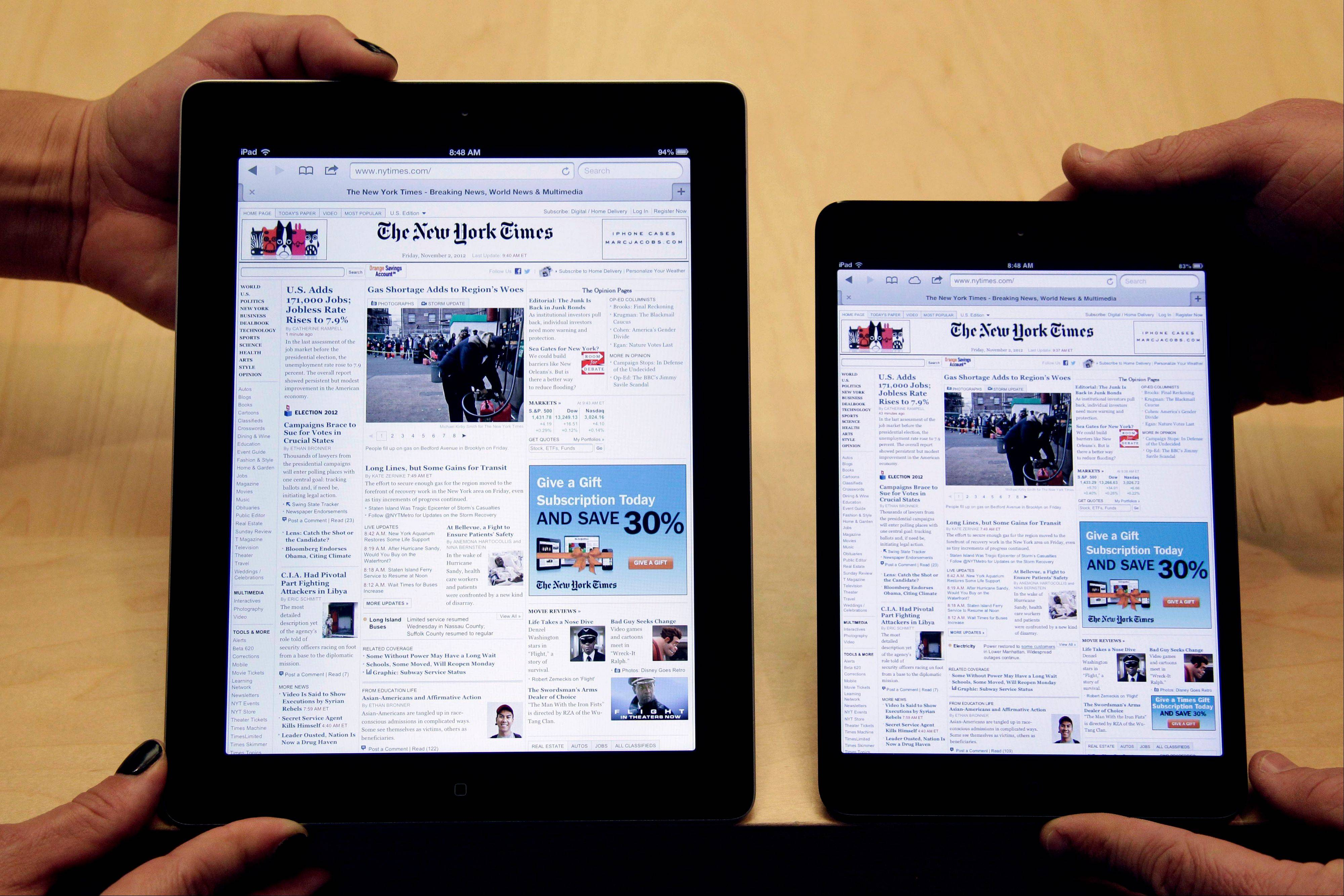 Employees hold a new full size Apple iPad 4th generation, left, next to new Apple iPad mini at the Apple store on Michigan Ave. in Chicago. Farhad Manjoo wants to know why Apple hasn't designed MacBooks to respond to touch like iPads.