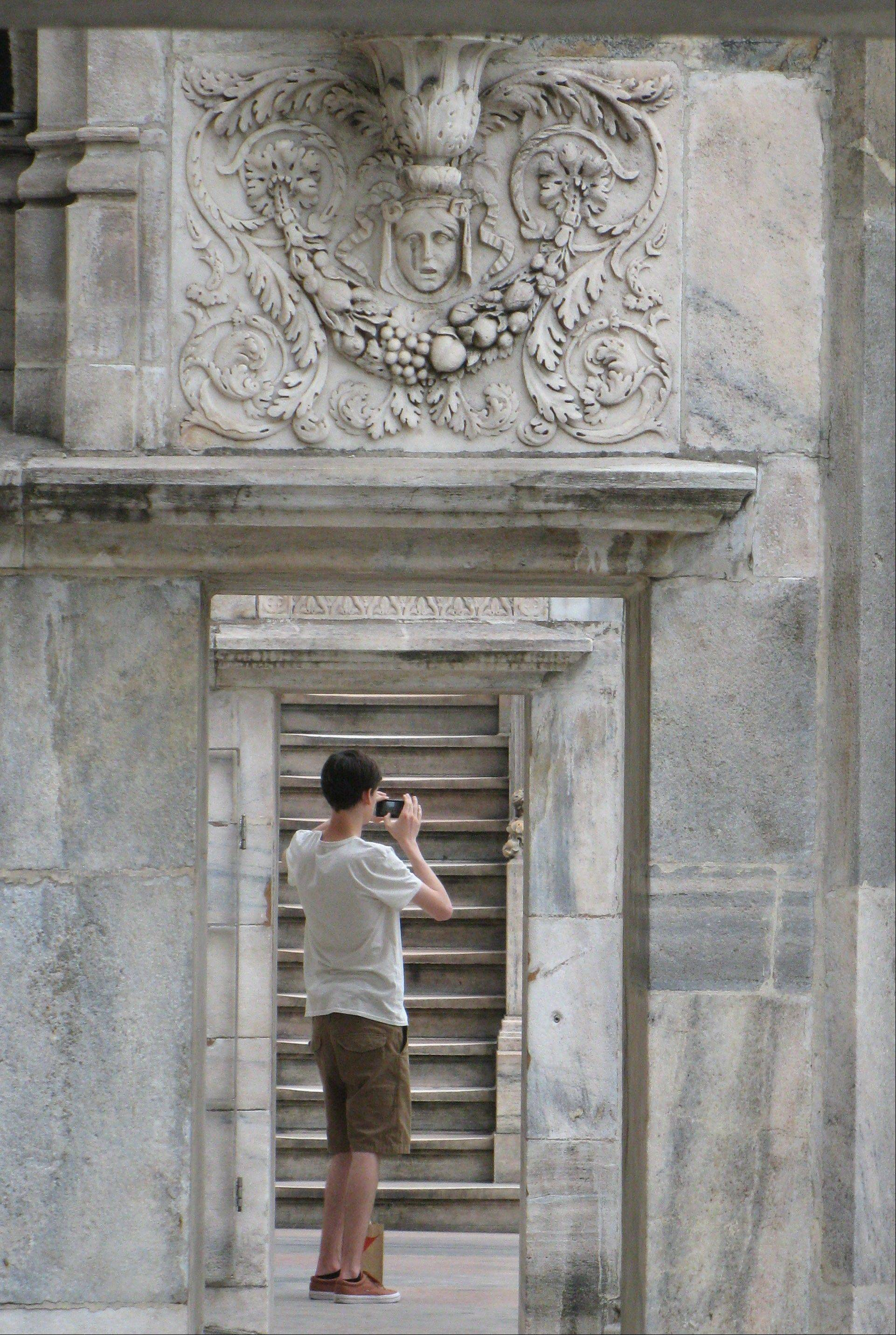 A man takes a picture on the rooftop of the Milan cathedral.